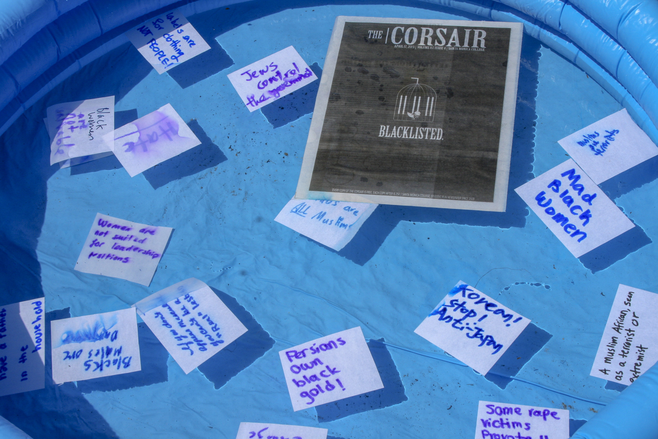 """Inflatable pool is used to drown words of oppression, hate, stigmas. """"Not On Our Campus"""" week , hosted by the A.S on main campus Santa Monica College, on April 18, 2019. (The Corsair/ Janet Ali)"""