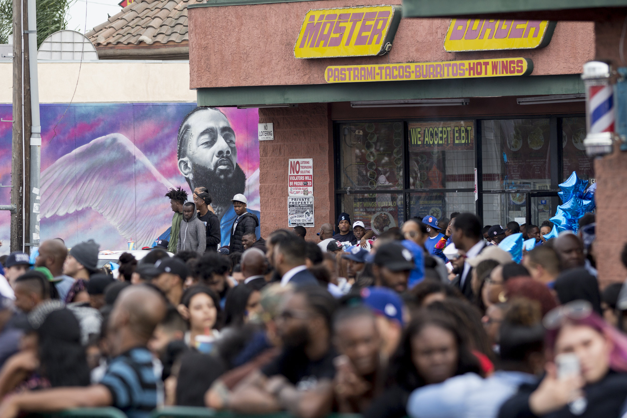 """Fans fill the parking lot of The Marathon Clothing store and turn out in numbers along Slauson Avenue to say goodbye to in Los Angeles, California on April 11, 2019.  The hearse carrying the casket of the slain rapper, Nipsey Hussle, will journey a 25.5 mile """"Victory Lap"""" through South Central and ending at the Angelus Funeral home to allow his fans, who could not attend the ceremony, to say goodbye.  (Jose Lopez)"""