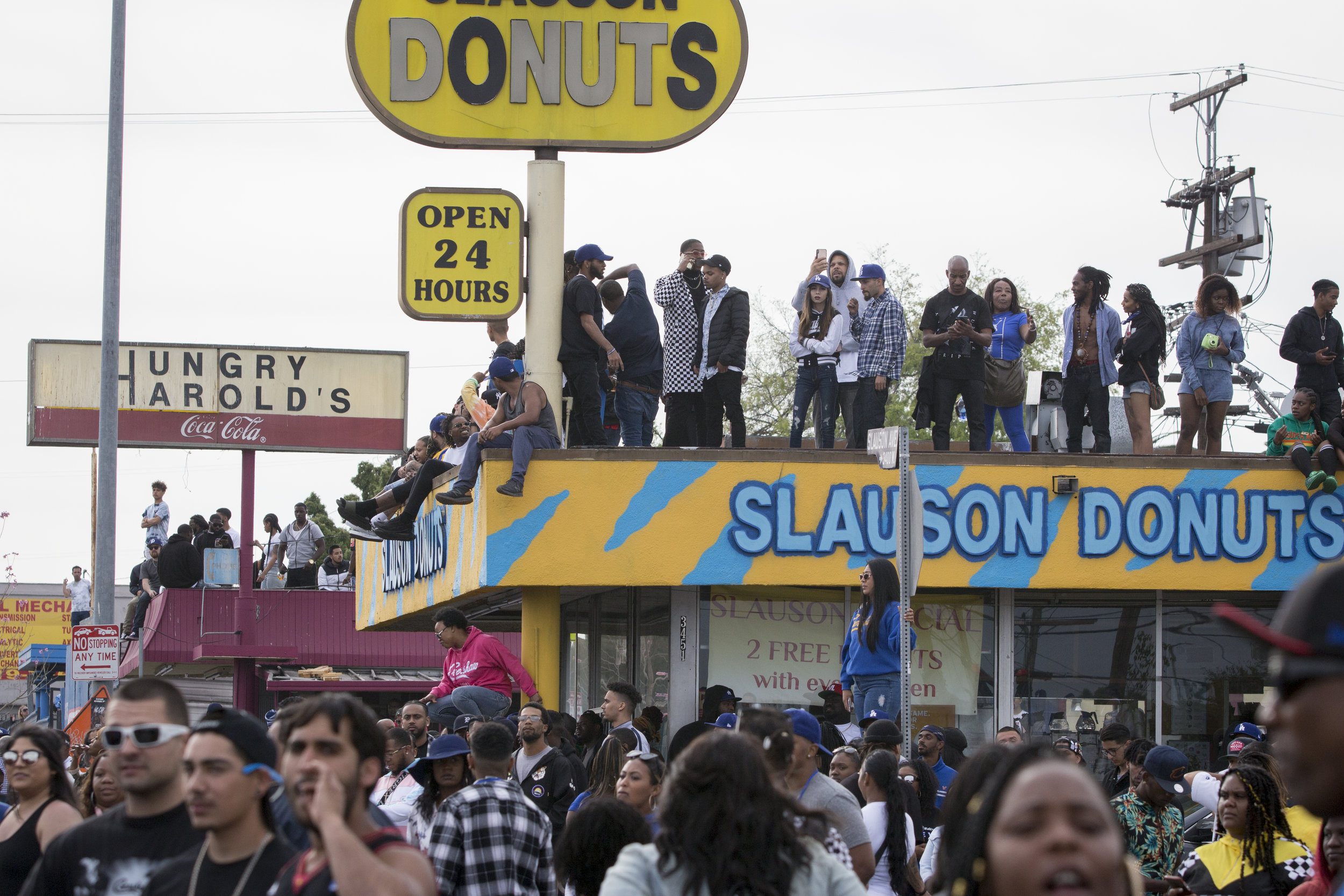 """Fans take to the roofs of businesses and homes as they wait for the Celebration of Life procession carrying the casket of Nipsey Hussle to ride down Slauson in Los Angeles, California on April 11, 2019.  The hearse carrying the casket of the slain rapper, Nipsey Hussle, will journey a 25.5 mile """"Victory Lap"""" through South Central and ending at the Angelus Funeral home to allow his fans, who could not attend the ceremony, to say goodbye.  (Jose Lopez)"""