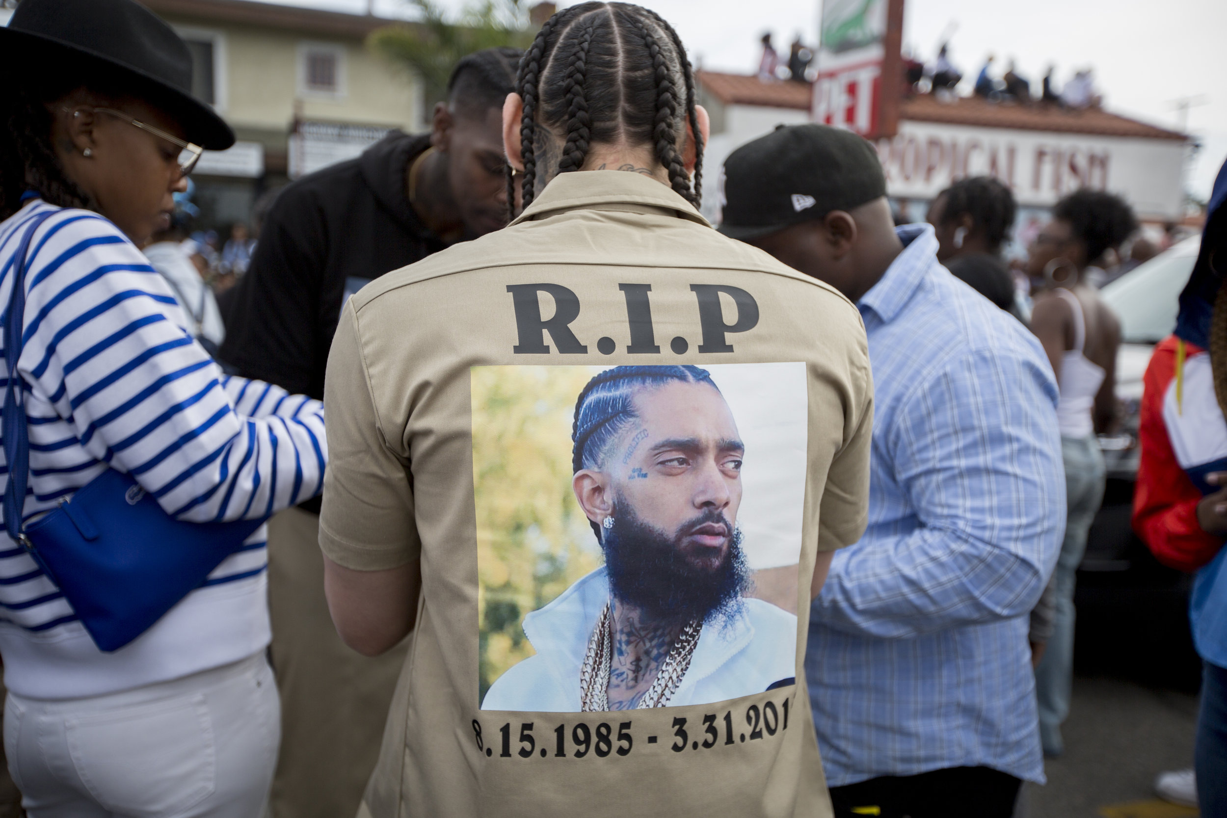 """Fans turn out to say goodbye to Nipsey Hussle, wearing his image on their clothing, along Slauson Avenue in Los Angeles, California on April 11, 2019.  The hearse carrying the casket of the slain rapper, Nipsey Hussle, will journey a 25.5 mile """"Victory Lap"""" through South Central and ending at the Angelus Funeral home to allow his fans, who could not attend the ceremony, to say goodbye.  (Jose Lopez)"""