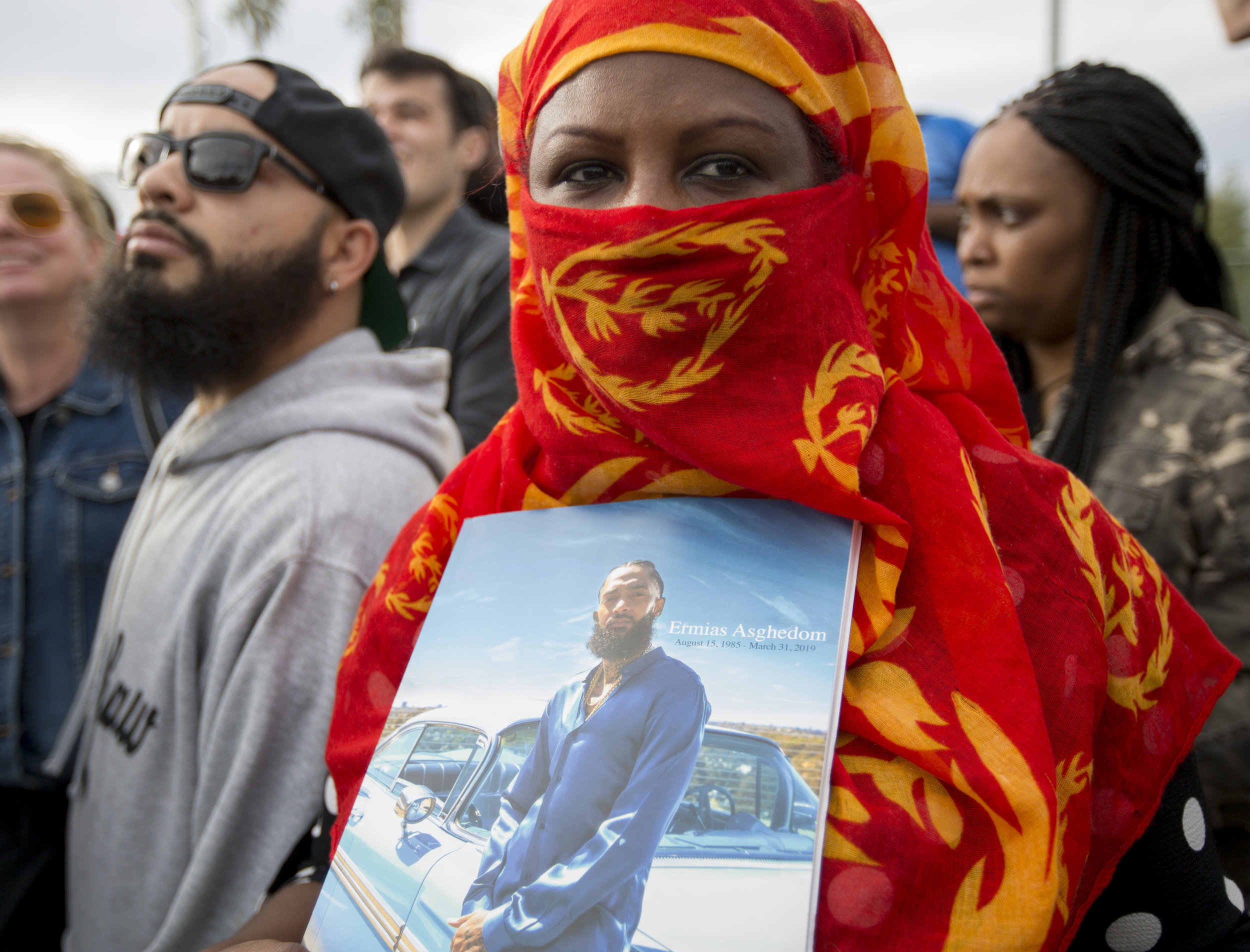 """Hermon Fessahaye holds her program from the Celebration of Life memorial service as she waits in the crowd for the procession to drive along Slauson Avenue so she can say goodbye to fellow Eritrean, Nipsey Hussle, in Los Angeles, California on April 11, 2019. She feels a particular connection to Nipsey Hussle's story because she said her brother, Sador Fessahaye also known as """"Sandman Nugus"""" , who was a friend of Nipsey's and fellow rapper, was also tragically killed in the same way. She feels almost as if she is reliving the tragedy in response she felt it was important to come out and show support to Nipsey's family. Hermon Fessahaye, who fought in the civil war back home in Eritrea, wants to see the gangs stop killing each other because she has seen war and how it destroys lives. She said, """"Stop destroying family. I've seen too many deaths in the street. It's a cemetery."""" (Jose Lopez)"""