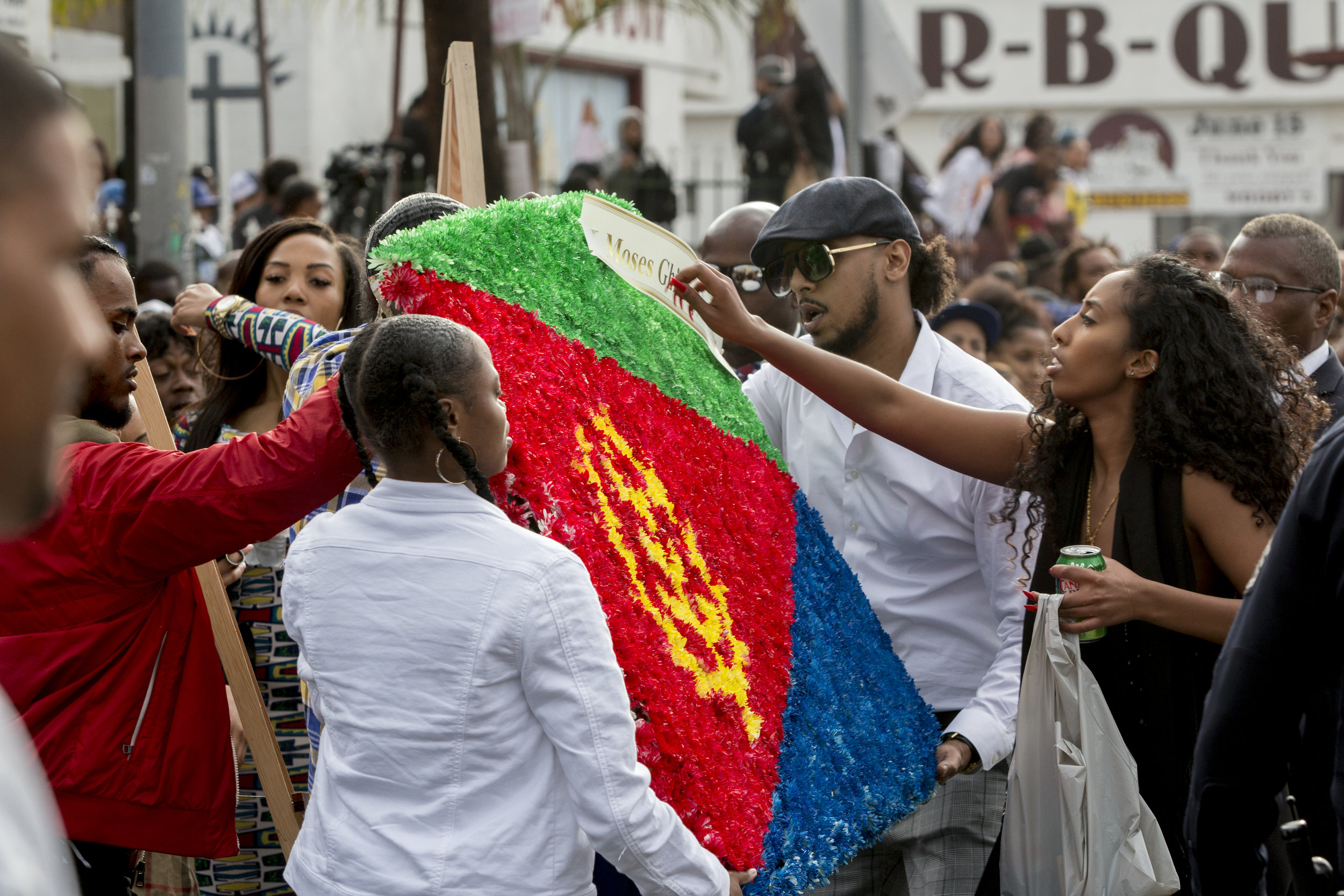 """Members of the Eritrean community prepare a display of flowers arranged as the Eritrean flag to honor the slain rapper Nipsey Hussle during the Celebration of Life procession that will be carrying his casket down Slauson in Los Angeles, California on April 11, 2019.  The hearse carrying the casket of the slain rapper, Nipsey Hussle, will journey a 25.5 mile """"Victory Lap"""" through South Central and ending at the Angelus Funeral home to allow his fans, who could not attend the ceremony, to say goodbye.  (Jose Lopez)"""