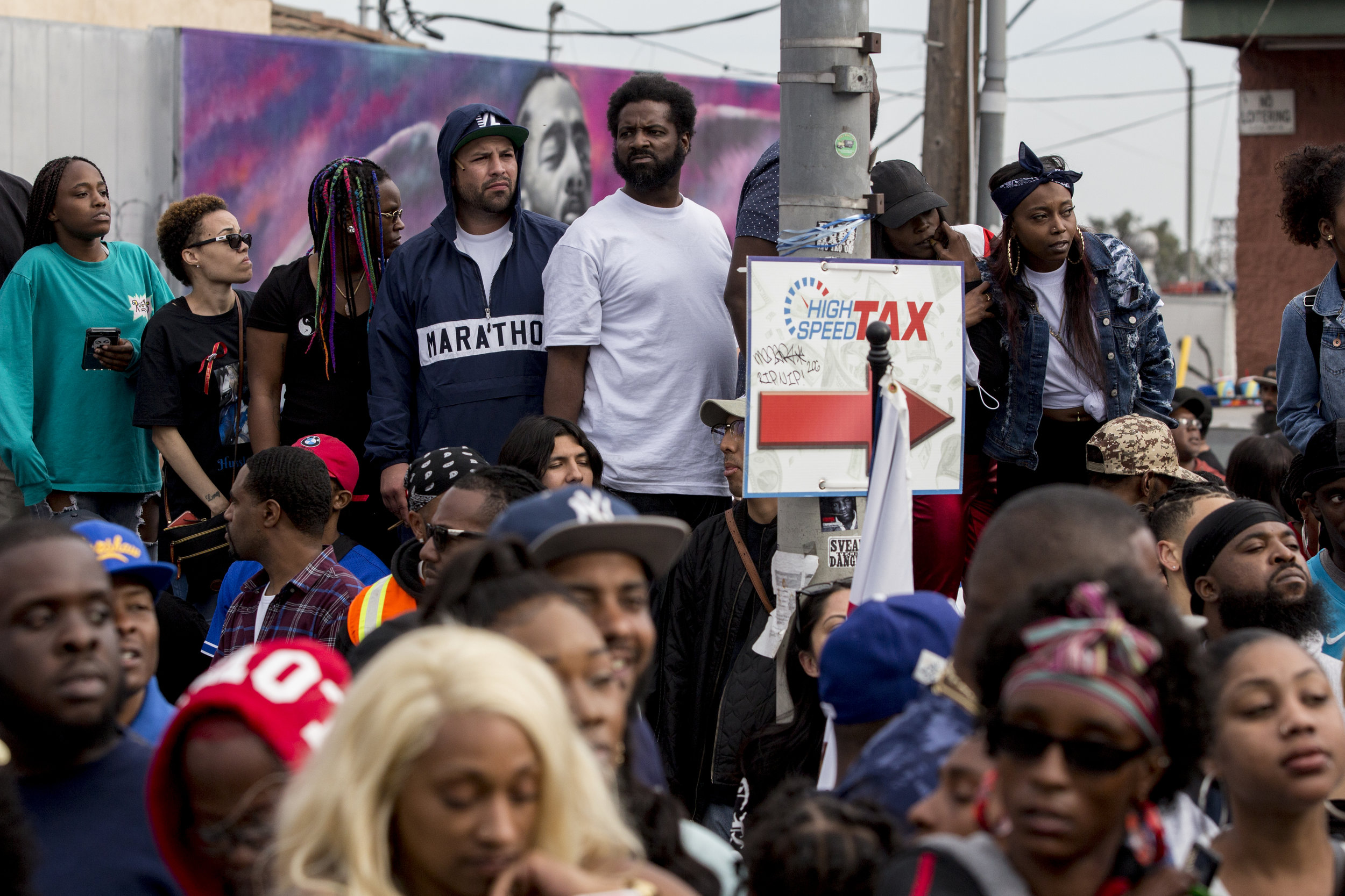 """Fans turn out to say goodbye to Nipsey Hussle with a mural of his image at their backs along Slauson Ave. near The Marathon Clothing store, the location of his murder, in Los Angeles, California on April 11, 2019.  The hearse carrying the casket of the slain rapper, Nipsey Hussle, will journey a 25.5 mile """"Victory Lap"""" through South Central and ending at the Angelus Funeral home to allow his fans, who could not attend the ceremony, to say goodbye.  (Jose Lopez)"""