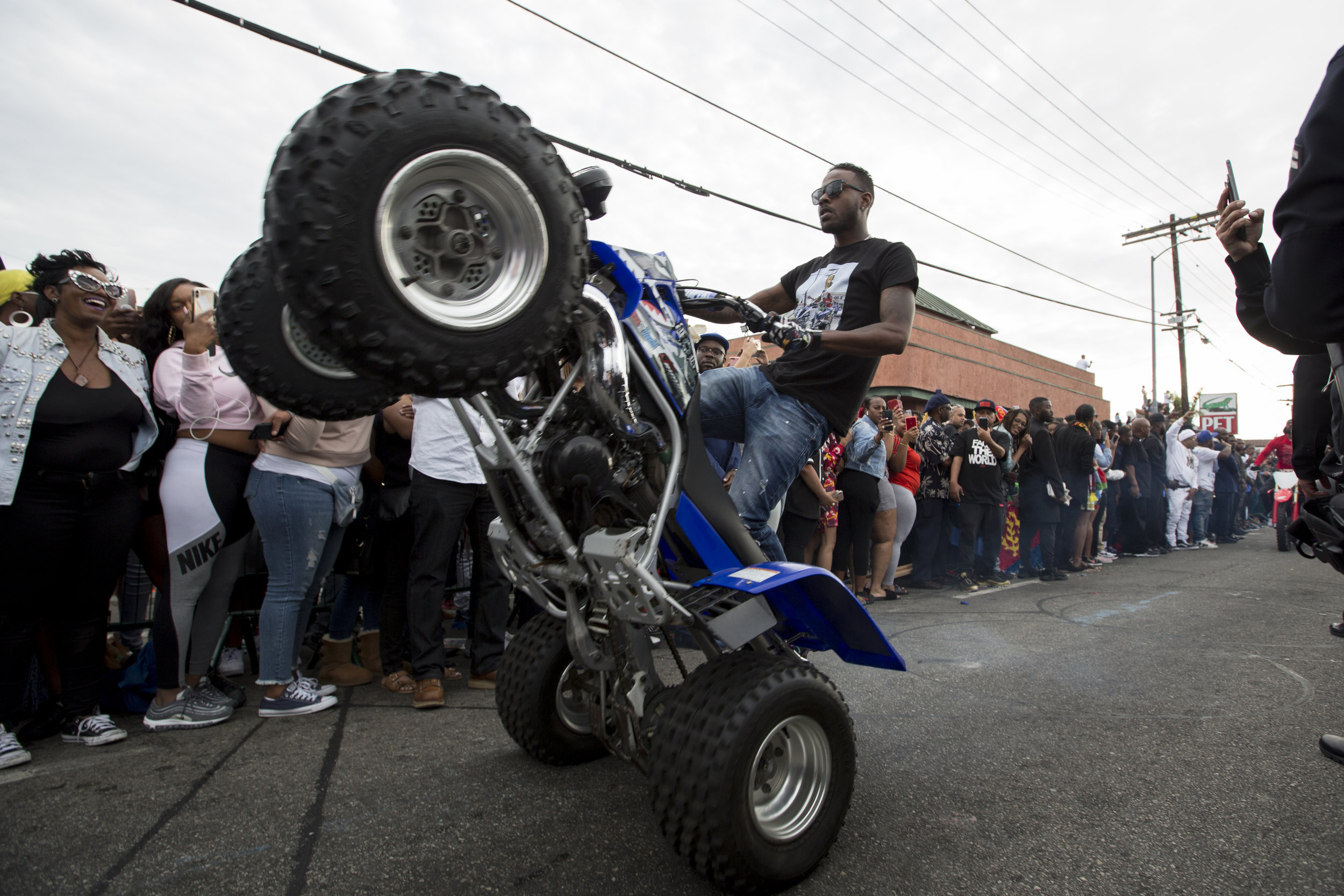 """An ATV pulls a wheelie in front of fans who turned out for the Celebration of Life procession to say goodbye to Nipsey Hussle along Slauson Ave. near The Marathon Clothing store, the location of his murder, in Los Angeles, California on April 11, 2019.  The hearse carrying the casket of the slain rapper, Nipsey Hussle, will journey a 25.5 mile """"Victory Lap"""" through South Central and ending at the Angelus Funeral home to allow his fans, who could not attend the ceremony, to say goodbye.  (Jose Lopez)"""