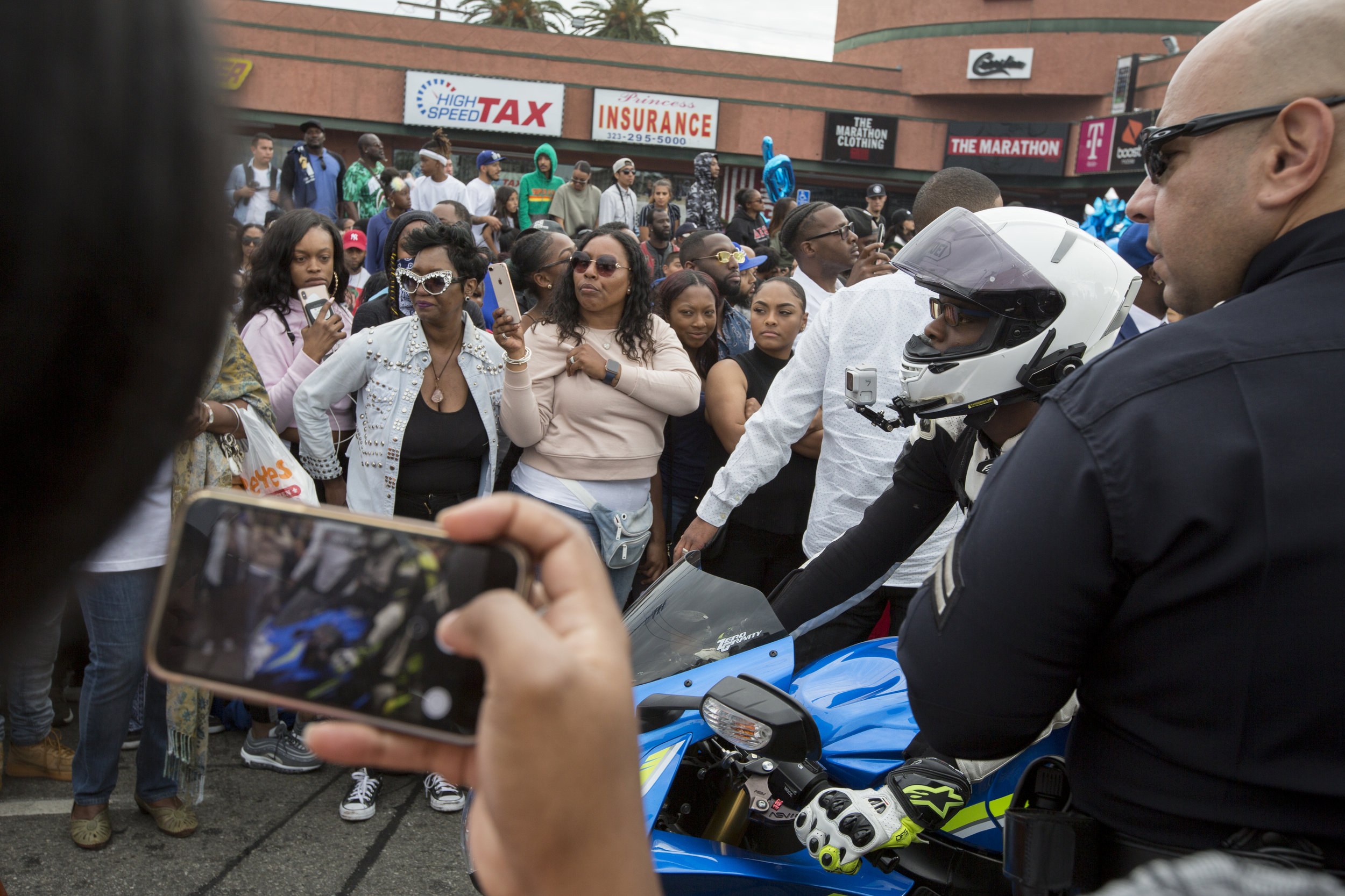 """Fans turn out for the Celebration of Life procession to say goodbye to Nipsey Hussle along Slauson Ave. near The Marathon Clothing store, the location of his murder, in Los Angeles, California on April 11, 2019.  The hearse carrying the casket of the slain rapper, Nipsey Hussle, will journey a 25.5 mile """"Victory Lap"""" through South Central and ending at the Angelus Funeral home to allow his fans, who could not attend the ceremony, to say goodbye.  (Jose Lopez)"""