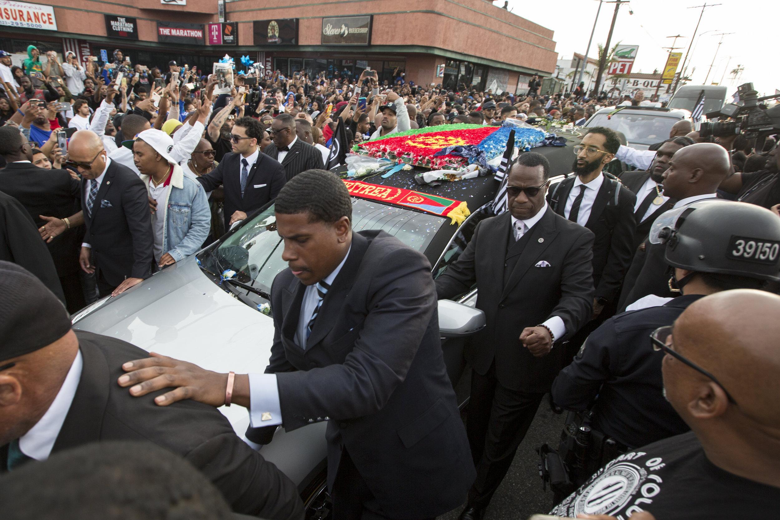 """Samiel """"Blacc Sam"""" Asghedom (right) walks alongside the hearse carrying his brother, slain rapper Nipsey Hussle, during the Celebration of Life procession  along Slauson Ave. near The Marathon Clothing store, the location of his murder, in Los Angeles, California on April 11, 2019.  The hearse carrying the casket of, Nipsey Hussle, will journey a 25.5 mile """"Victory Lap"""" through South Central and ending at the Angelus Funeral home to allow his fans, who could not attend the ceremony, to say goodbye.  (Jose Lopez)"""