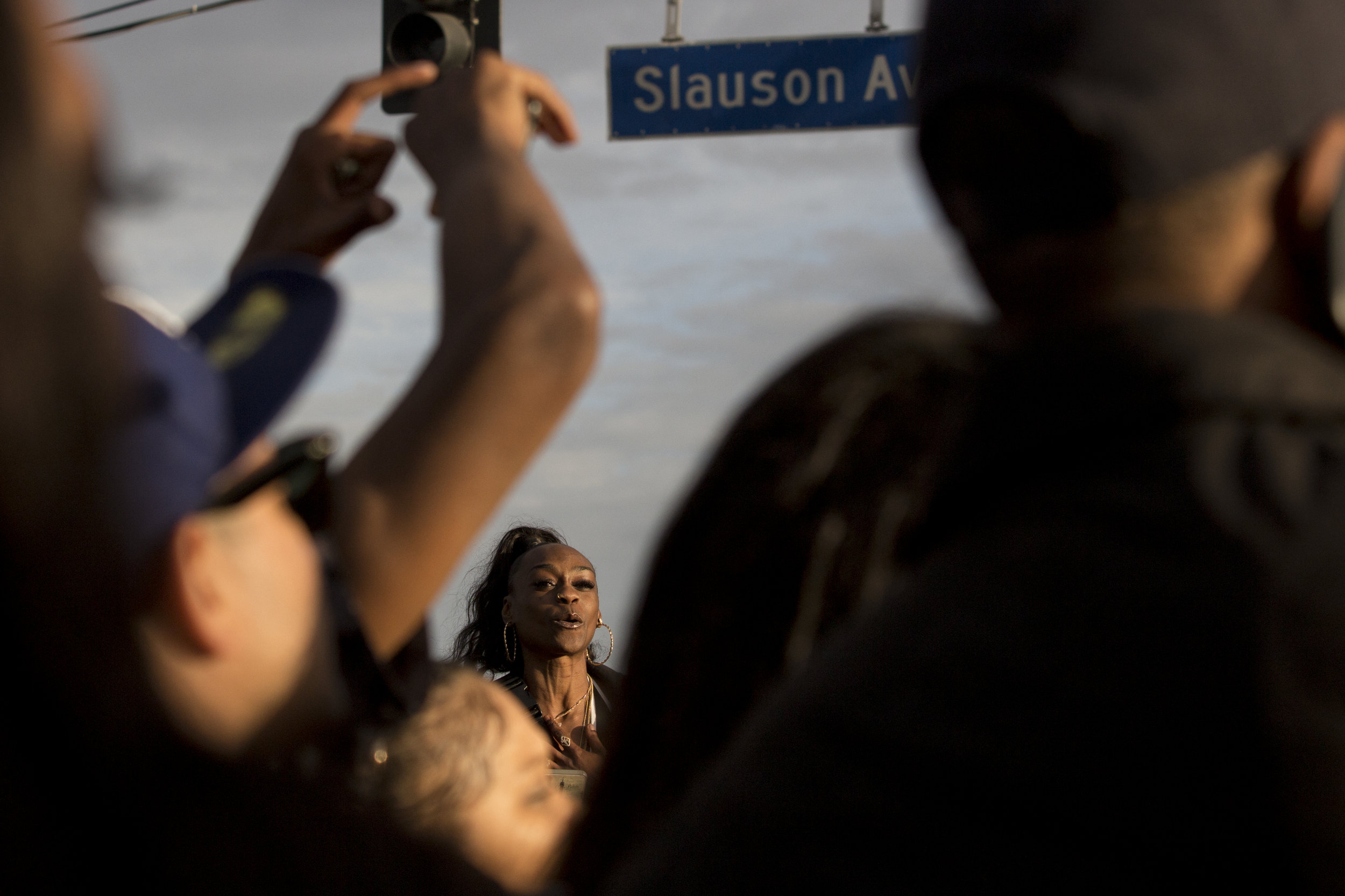 """A woman cheers loudly as the Celebration of Life procession carrying the casket of Nipsey Hussle moves closer to the intersection of Crenshaw Blvd. and Slauson Ave. in Los Angeles, California on April 11, 2019.  The hearse carrying the casket of the slain rapper, Nipsey Hussle, will journey a 25.5 mile """"Victory Lap"""" through South Central to allow his fans, who could not attend the ceremony, to say goodbye.  (Jose Lopez)"""