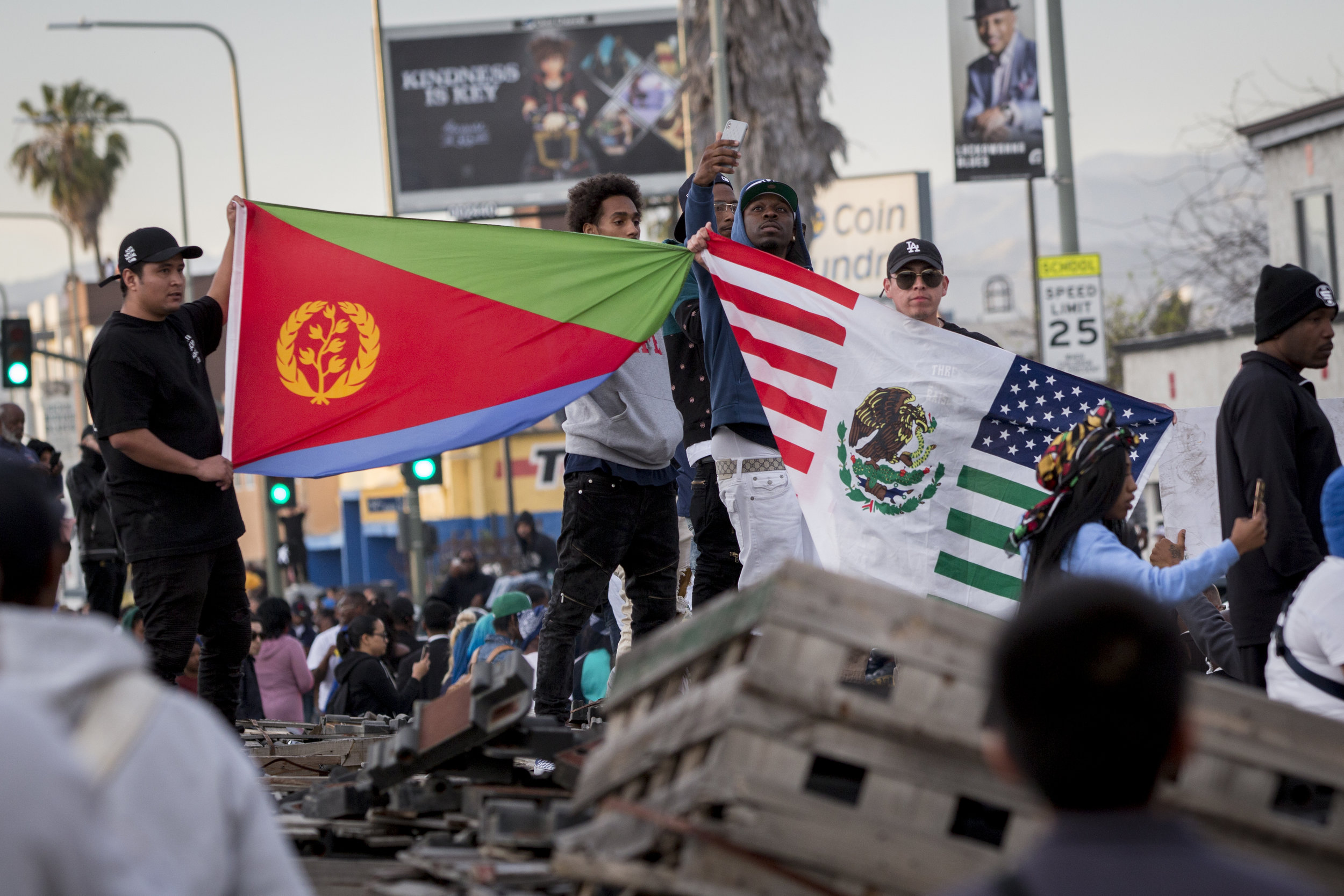 """Fans, holding up unified Eritrean and Mexican flags, turn out to say goodbye to Nipsey Hussle as the Celebration of Life procession rides down Crenshaw Blvd. in Los Angeles, California on April 11, 2019.  The hearse carrying the casket of the slain rapper, Nipsey Hussle, will journey a 25.5 mile """"Victory Lap"""" through South Central to allow his fans, who could not attend the ceremony, to say goodbye.  (Jose Lopez)"""