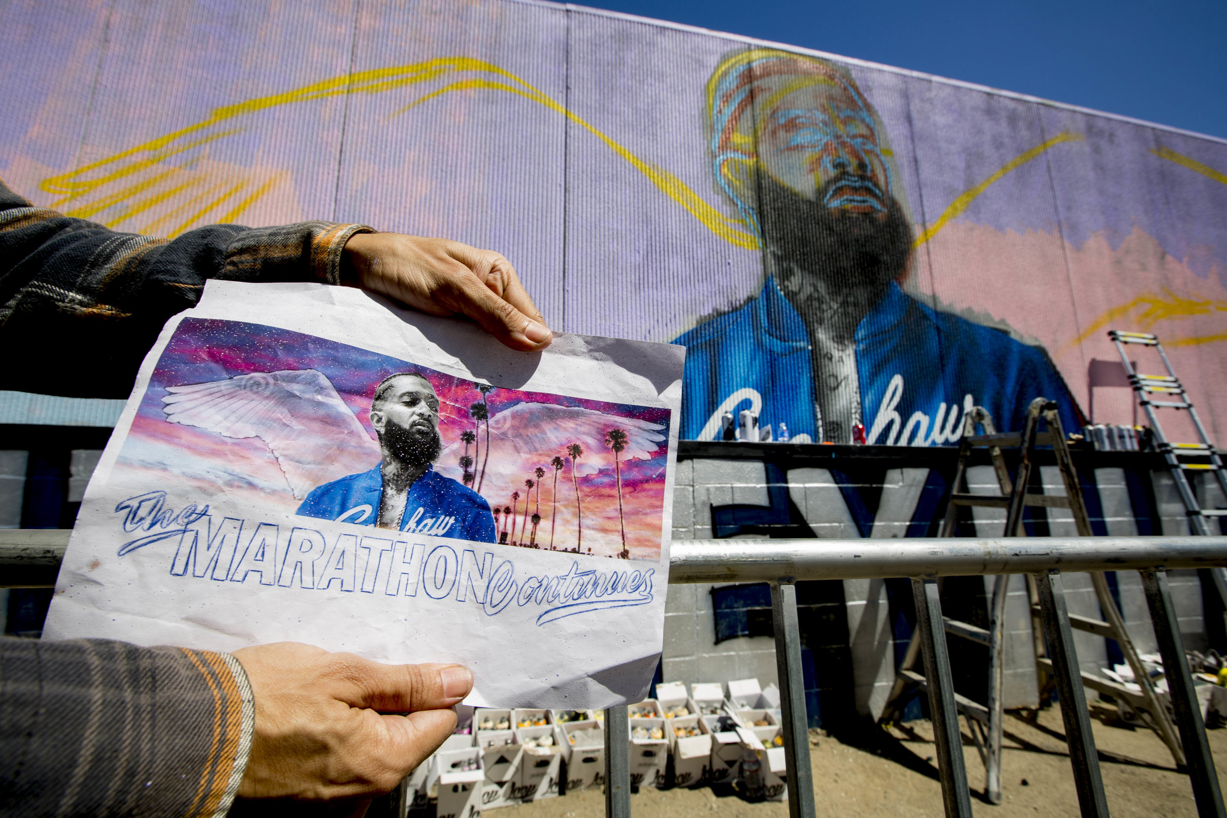 """Daniel Mateo and his crew pay their respects to Nipsey by painting a mural on a wall in the alley near The Marathon Clothing store off of Slauson Avenue and Crenshaw Boulevard in Los Angeles, California on April 6, 2019. Mateo said that it all started when he shared the idea with Nipsey's family, which they really loved, allowing him to start production. The mural is a labor of love and respect, by Mateo, as he responded by sharing that he is there doing it for free and not charging for the work. He said, """"We gotta show our respect for Nipsey."""" When asked if he sees himself embracing any of the principles that Nipsey was popularizing, Mateo said that, """"In a way we're all living his life. We are daily hustling, grinding. Hopefully we can take some of his knowledge and help out others, whether it be the community, small organizations. Anything that can pretty much help each other out. Yea, I'm pretty sure ill be doing that."""" (Jose Lopez)"""