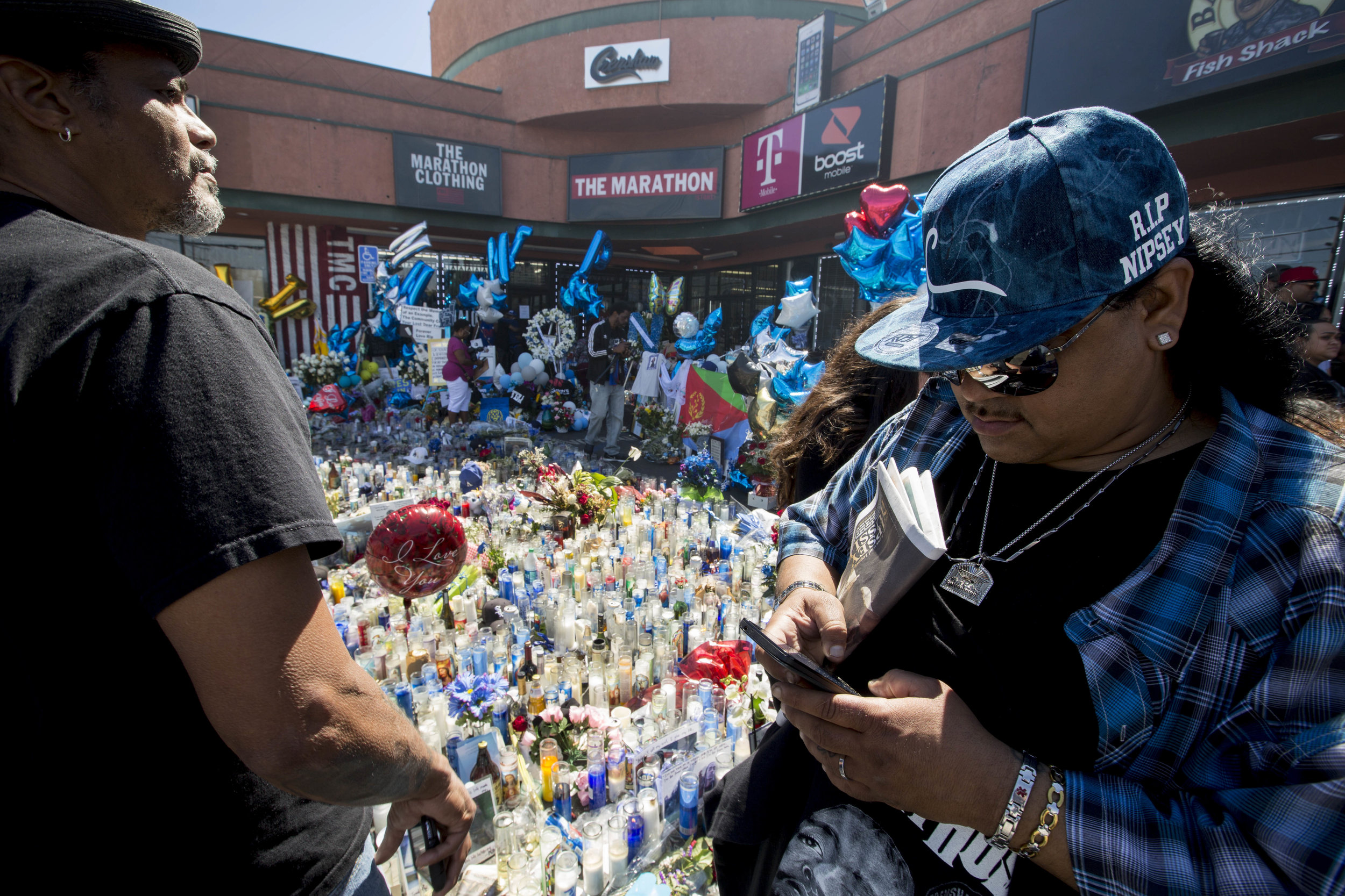 """Cali Rodriguez (right) visits Nipsey Hussle's memorial at The Marathon Clothing store on Slauson Avenue in Los Angeles, California on Wednesday, April 6, 2019. When asked how Nipsey made him feel, Rodriguez stated that, """"Nipsey was uplifting, man, because he gave back to the community. How many people do you know that get a taste of fame and come back and give back to your community? He was just a genuine good-hearted person.""""  The 33-year-old rapper was murdered on March 31 in front of The Marathon Clothing store which he owned. (Jose Lopez)"""