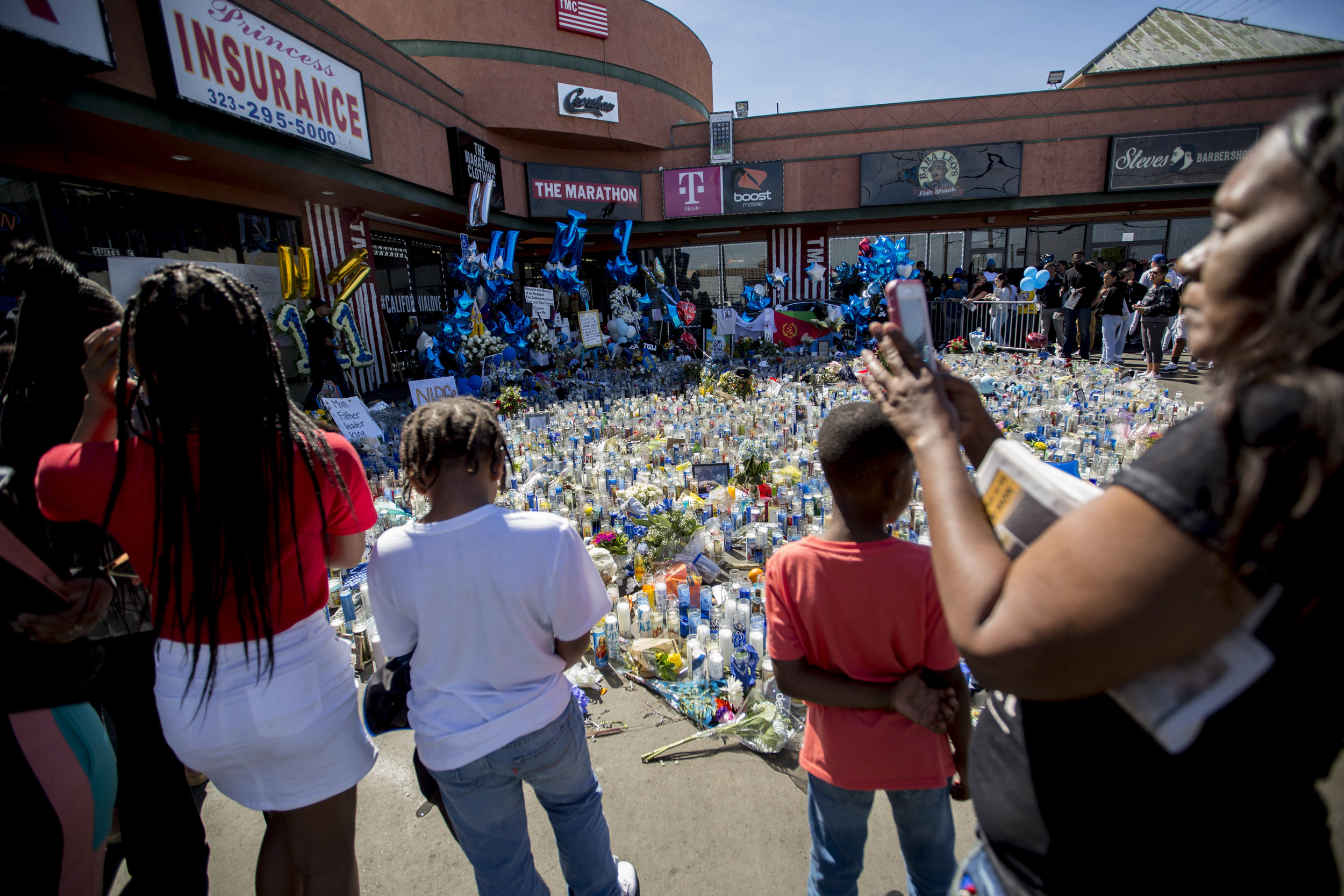 People visit Nipsey Hussle's memorial at The Marathon Clothing store on Slauson Avenue in Los Angeles, California on Wednesday, April 6, 2019. The 33-year-old rapper was murdered on March 31 in front of The Marathon Clothing store which he owned. (Jose Lopez)