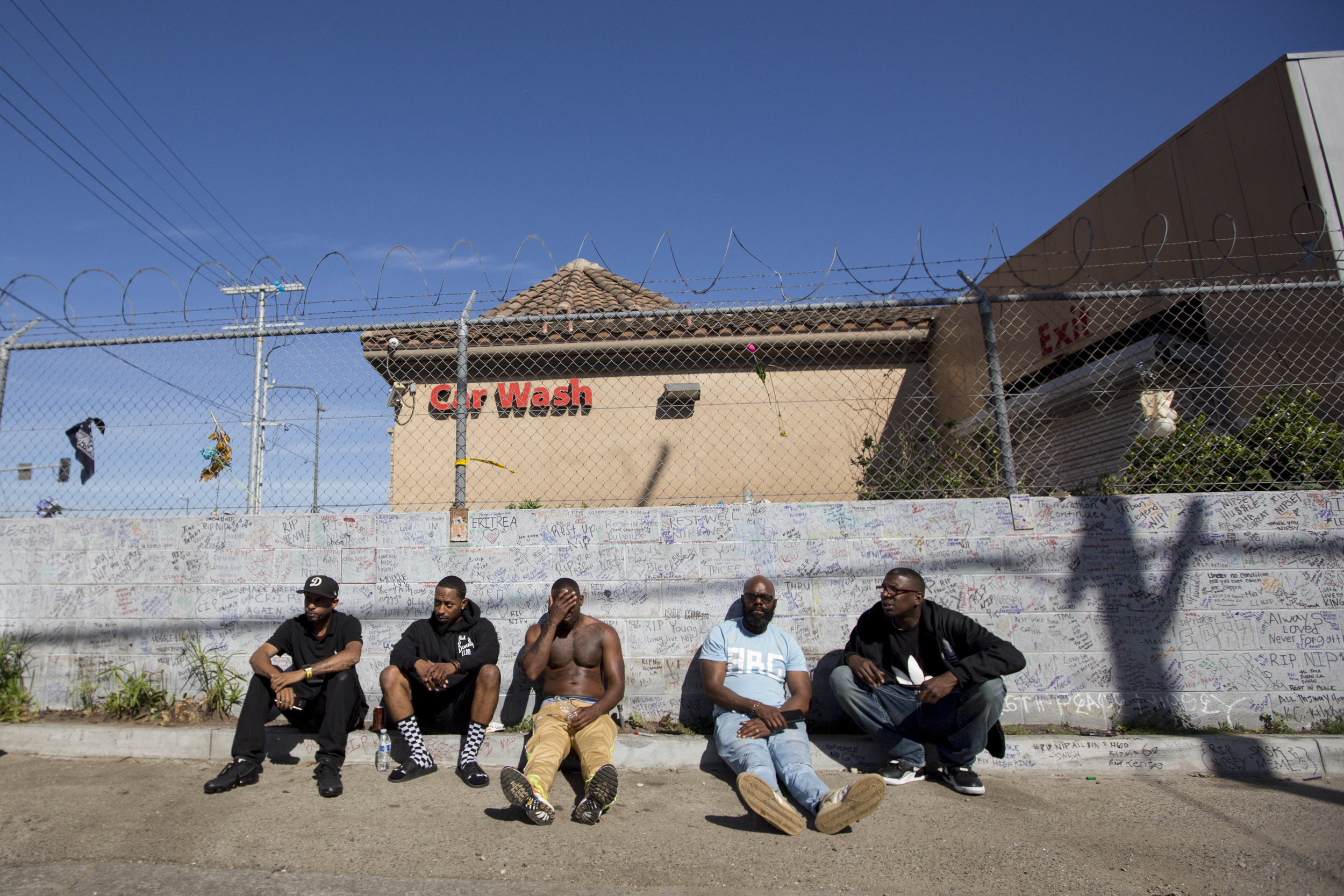 People attending the makeshift memorial for Nipsey Hussle sit back along a wall that is filled with hand written messages commemorating the life of the slain rapper near The Marathon Clothing store on Slauson Avenue in Los Angeles, California on Wednesday, April 6, 2019. The 33-year-old rapper was murdered on March 31 in front of The Marathon Clothing store which he owned. (Jose Lopez)