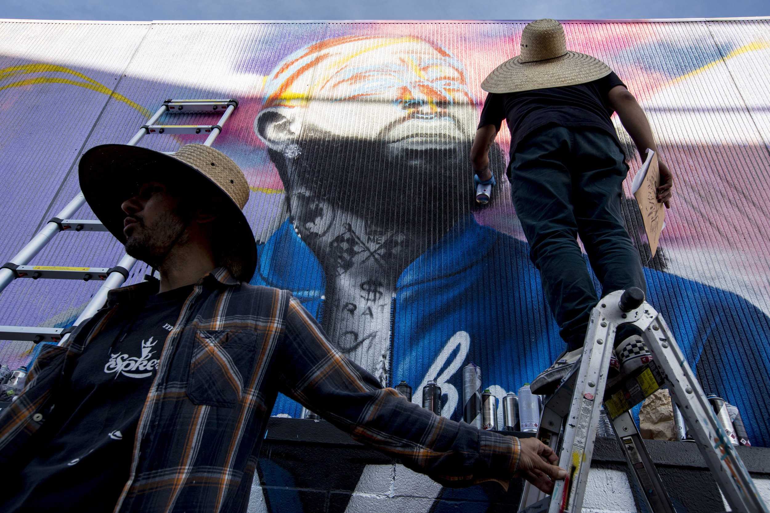 """Daniel Mateo and his crew pay their respects to Nipsey by painting a mural on a wall in the alley near The Marathon Clothing store off of Slauson Avenue and Crenshaw Boulevard in Los Angeles, California on April 6, 2019. Mateo said that it all started when he shared the idea with Hussle's family, which they really loved, allowing him to start production. The mural is a labor of love and respect, by Mateo, as he responded by sharing that he is there doing it for free and not charging for the work. He said, """"We gotta show our respect for Nipsey."""" When asked if he sees himself embracing any of the principles that Nipsey was popularizing, Mateo said that, """"In a way we're all living his life. We are daily hustling, grinding. Hopefully we can take some of his knowledge and help out others, whether it be the community, small organizations. Anything that can pretty much help each other out. Yea, I'm pretty sure ill be doing that."""" (Jose Lopez)"""