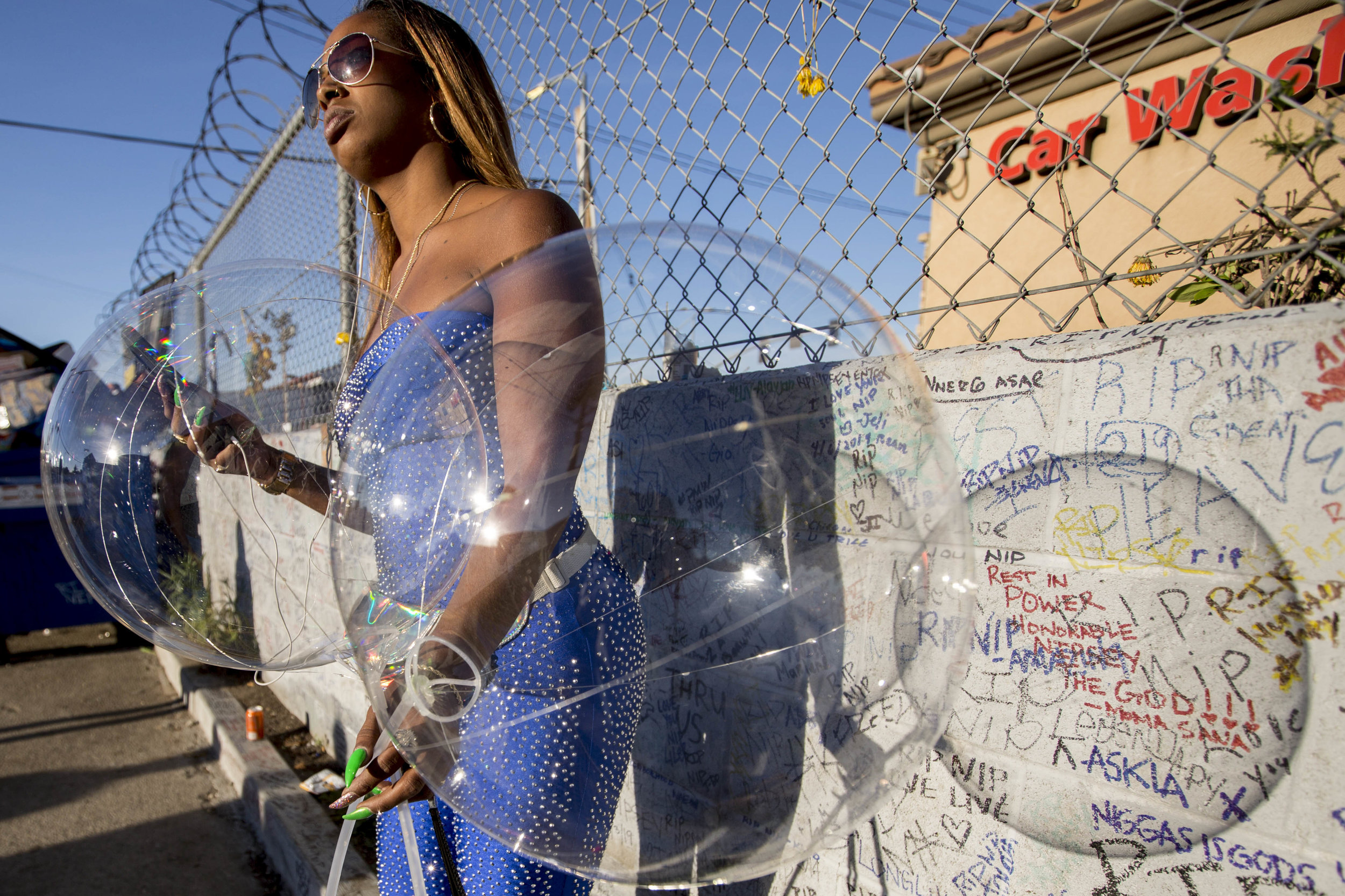 A woman waits for the sun to go down so that she can light up her clear balloons and place them at the makeshift memorial in commemoration of Nipsey Hussle at The Marathon Clothing store on Slauson Avenue in Los Angeles, California on Wednesday, April 6, 2019. The 33-year-old rapper was murdered on March 31 in front of The Marathon Clothing store which he owned. (Jose Lopez)
