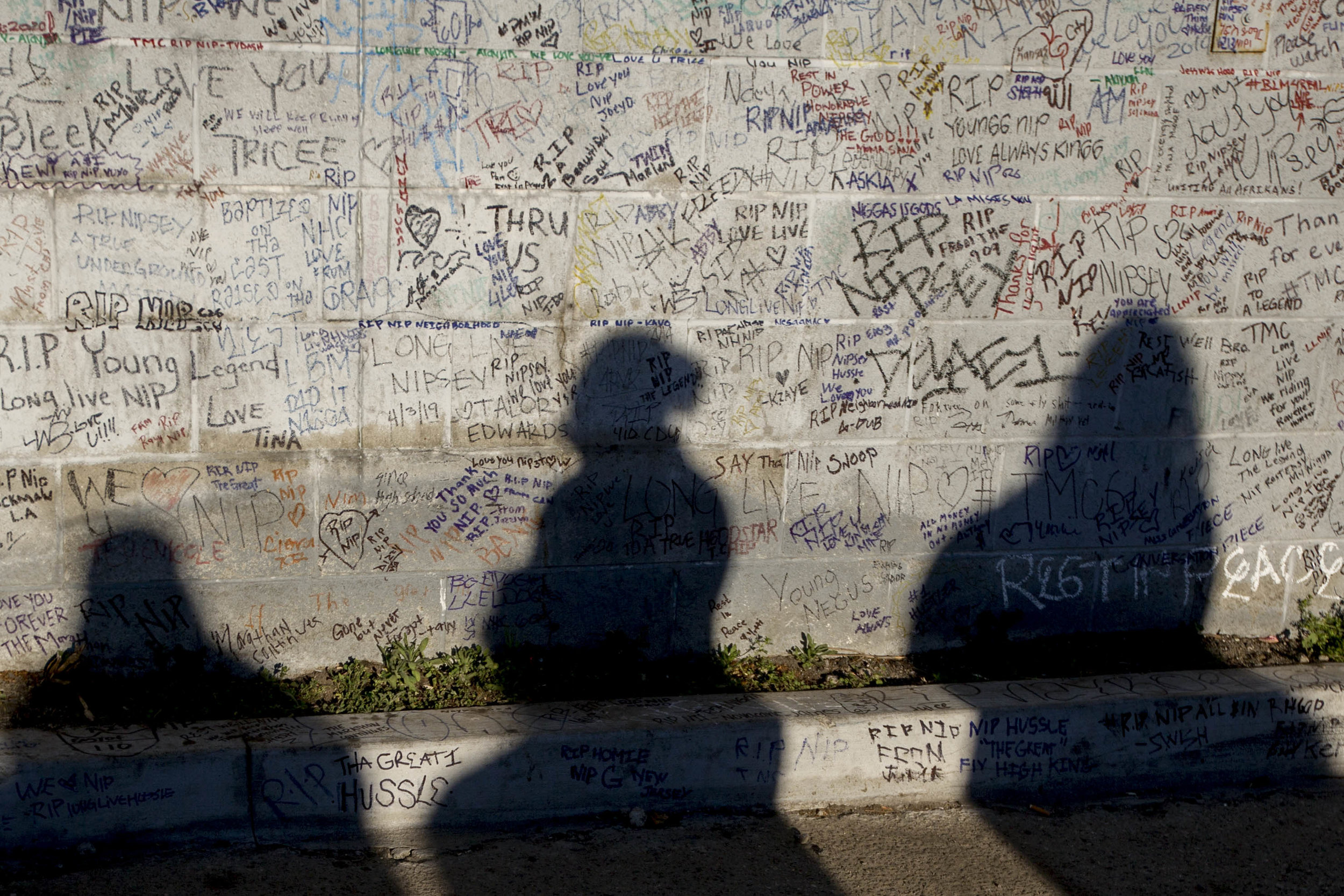 The shadows of people reading the many hand written messages commemorating the life of Nipsey Hussle are projected over a wall at the makeshift memorial near The Marathon Clothing store on Slauson Avenue in Los Angeles, California on Wednesday, April 6, 2019. The 33-year-old rapper was murdered on March 31 in front of The Marathon Clothing store which he owned. (Jose Lopez)
