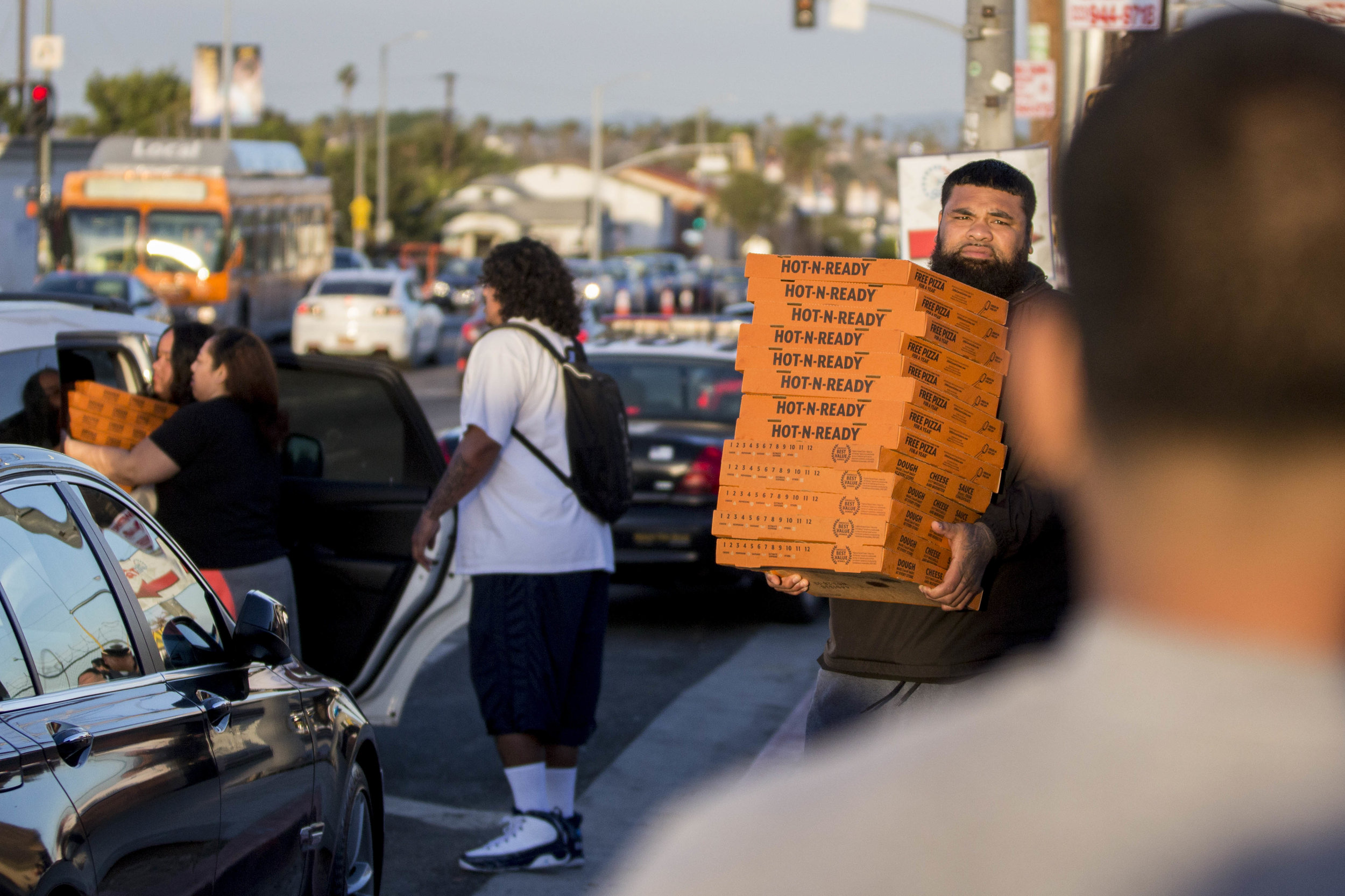 """A man helps unload a car and carries a stack of pizzas over to the area where a makeshift memorial honoring Nipsey Hussle is set up so they can feed all the family and fans who have come out to pay their respects to the slain rapper at The Marathon Clothing store in Los Angeles, California on April 6, 2010.  Renei Ngaue Fangupo along with her cousin and family wanted to do something to give back to the community, in the name of Nipsey Hussle who was known to be generous and very giving to the Tongan community. As a result they came out to the makeshift memorial on Tuesday, April 2 to set up a taco stand to feed people to keep their stomachs full and put their spirits at ease. It was from there that the idea grew and Vikashari Moala along with her family wanted to continue the give away by putting out the word that they would be back on Saturday. Over a 100 people participated in the giveaway which included around 300 pizzas, some sandwiches, chips, and sodas.  Fangupo said, """"We basically wanted people to feel free to come out and eat, in the same way that Nip welcomed everybody here at The Marathon Clothing store.""""  The 33-year-old rapper was murdered on March 31 in front of The Marathon Clothing store which he owned. (Jose Lopez)"""