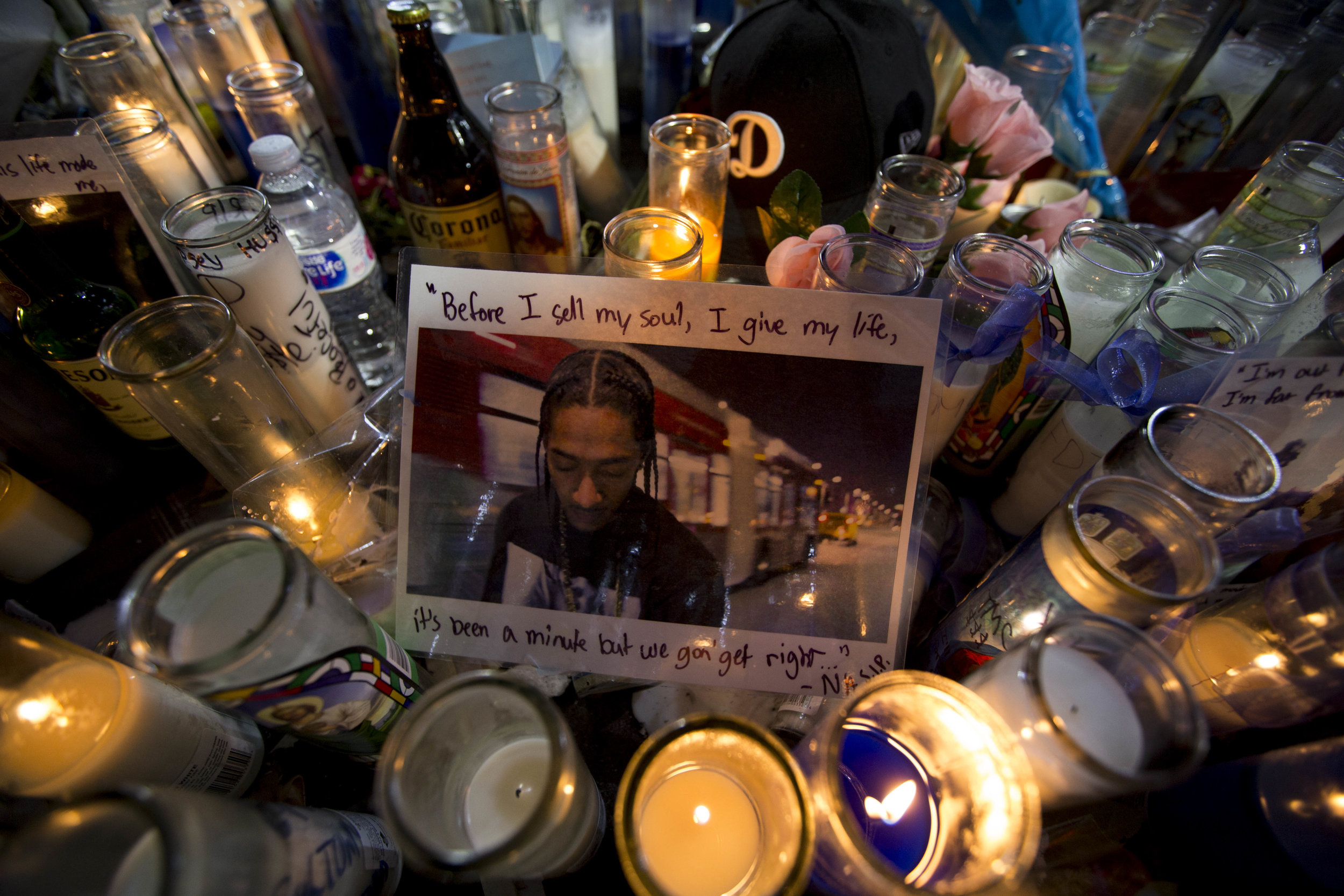 """Candles surround a photo of Nipsey Hussle that was placed at the makeshift memorial in front of The Marathon Clothing store off of Slauson Avenue and Crenshaw Boulevard in Los Angeles, California on April 6, 2019. The lyrics, """"Before I sell my soul, I give my life, It's been a minute but we gon' get right..."""" from his song """"Love"""" are written in the margins of the photo.  (Jose Lopez)"""