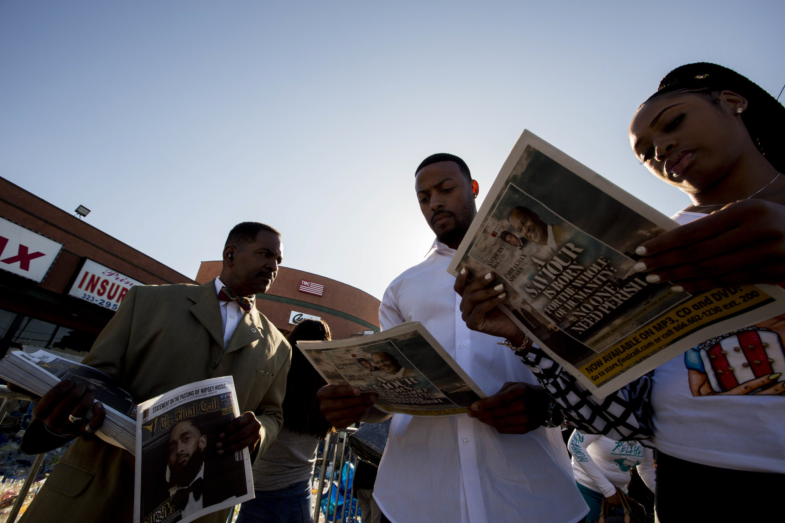 Nation of Islam members hand out copies of The Last Call newspaper, commemorating Nipsey Hussle on the cover, near the makeshift memorial at The Marathon Clothing store along Crenshaw Boulevard and Slauson Avenue in Los Angeles, California on Wednesday, April 10, 2019. The 33-year-old rapper was murdered on March 31 in front of The Marathon Clothing store which he owned. (Jose Lopez)