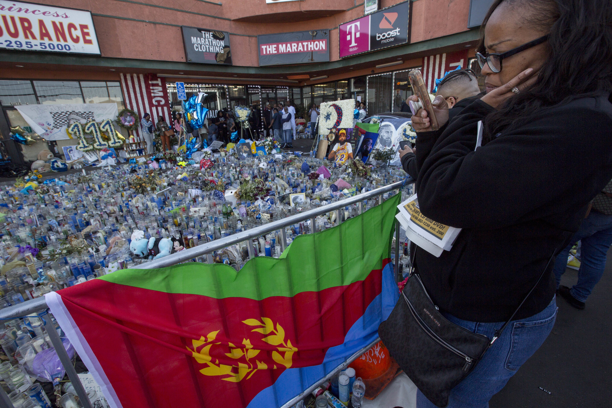A woman takes a photo of Nipsey Hussle's memorial at The Marathon Clothing store on Slauson Avenue in Los Angeles, California on Wednesday, April 10, 2019. The 33-year-old rapper was murdered on March 31 in front of The Marathon Clothing store which he owned. (Jose Lopez)