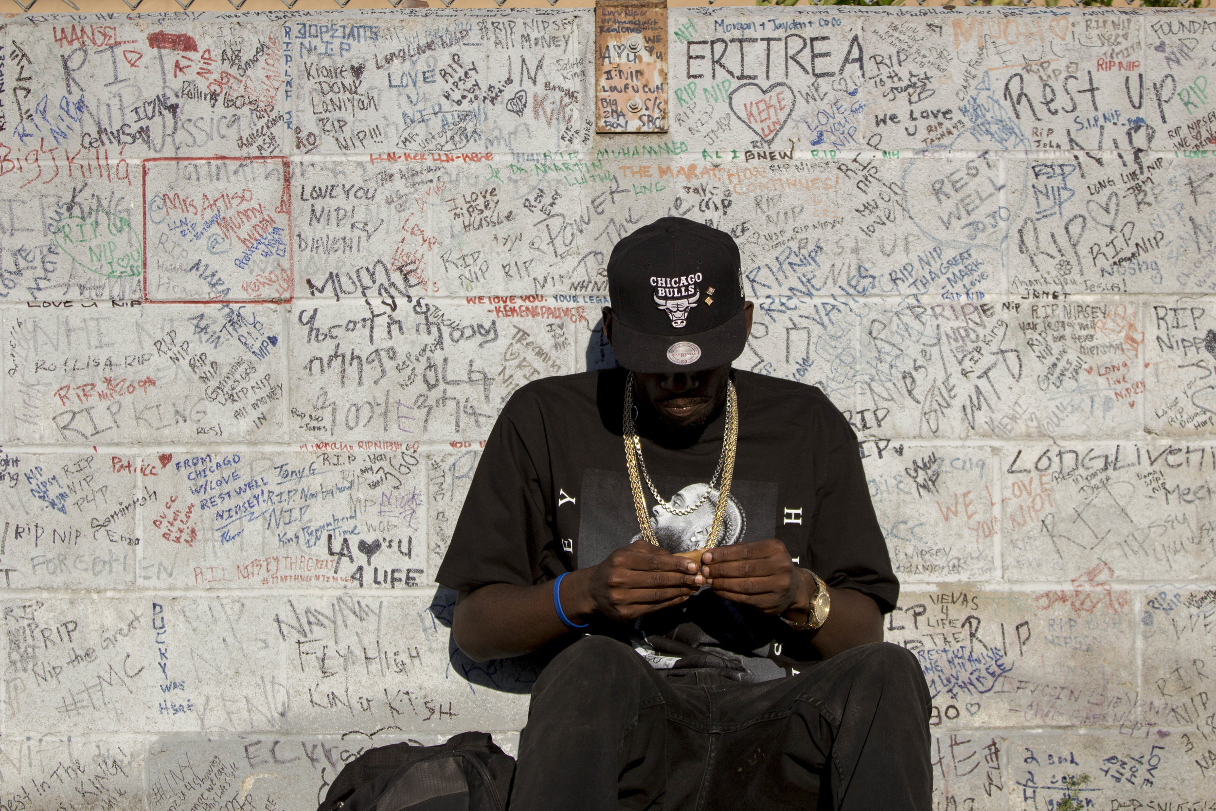 A fan sits near the wall filled with hand written messages commemorating the life of Nipsey Hussle at the makeshift memorial near The Marathon Clothing store on Slauson Avenue in Los Angeles, California on Wednesday, April 10, 2019. The 33-year-old rapper was murdered on March 31 in front of The Marathon Clothing store which he owned. (Jose Lopez)