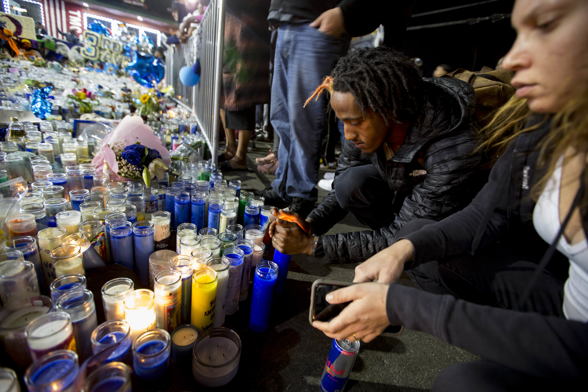 People light candles as they gather to commemorate the life of Nipsey Hussle at the makeshift memorial near The Marathon Clothing store on Slauson Avenue in Los Angeles, California on Wednesday, April 6, 2019. The 33-year-old rapper was murdered on March 31 in front of The Marathon Clothing store which he owned. (Jose Lopez)