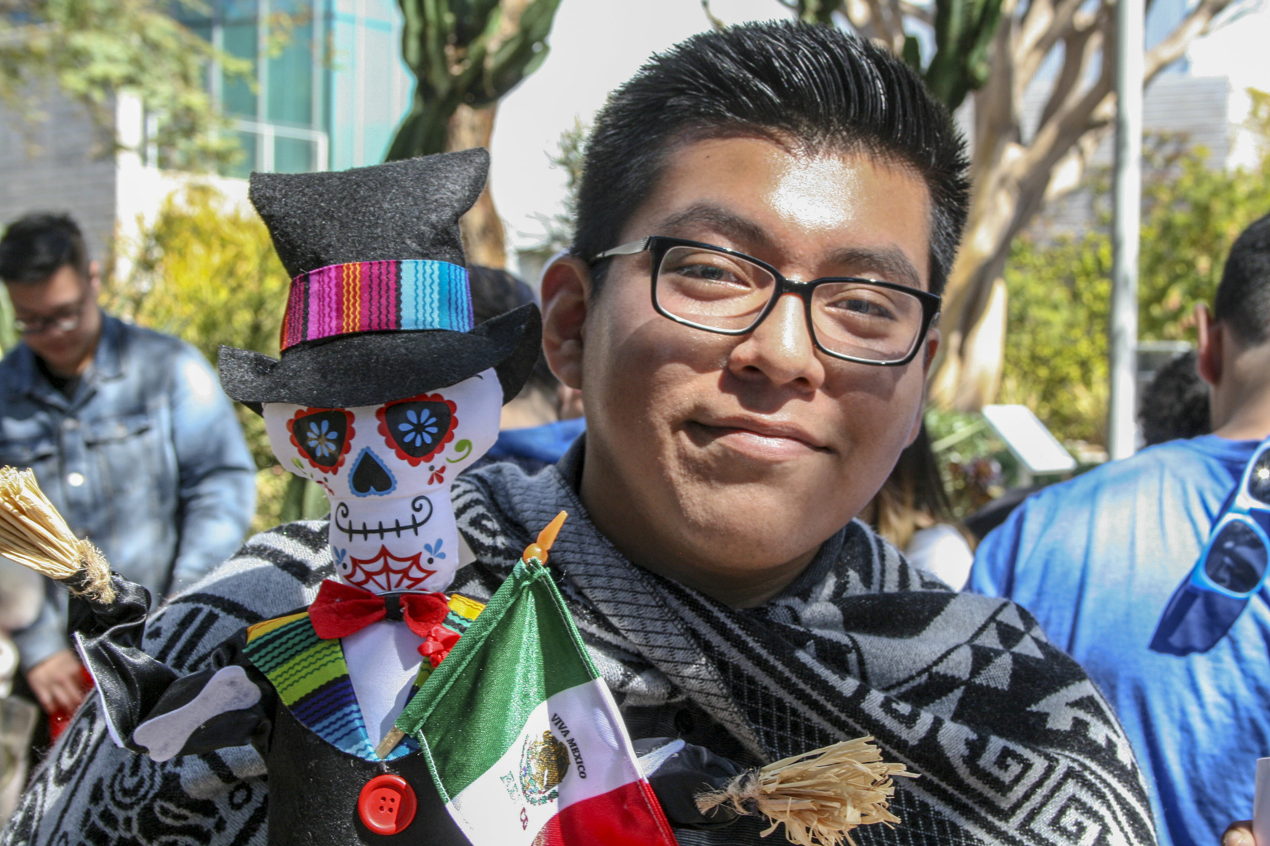 """Luis Florencio from the adelante club walks with a Mexican flag and a """"Dia de Muertos"""" skull. The club awarness day at main campus Santa Monica College, March 28 2019."""
