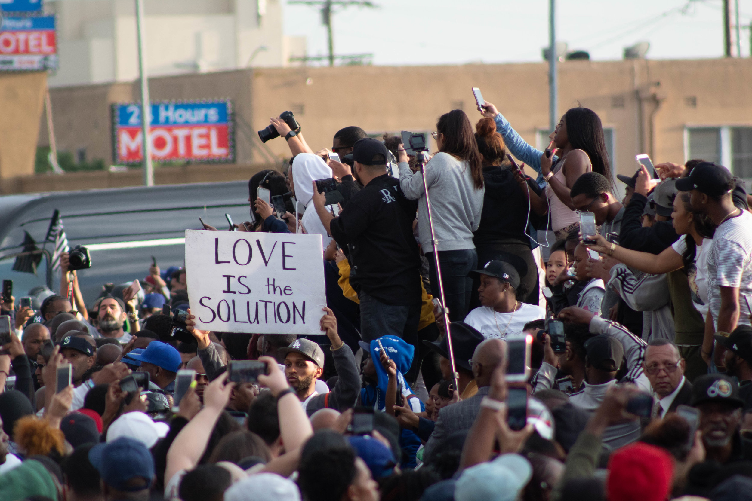 A crowd that filled the intersection of Crenshaw Boulevard and Slauson Avenue in South Los Angeles, California during the funeral procession of the late rapper Nipsey Hussle on Thursday, April 11, 2019. (Catherine Lima/Corsair Staff)