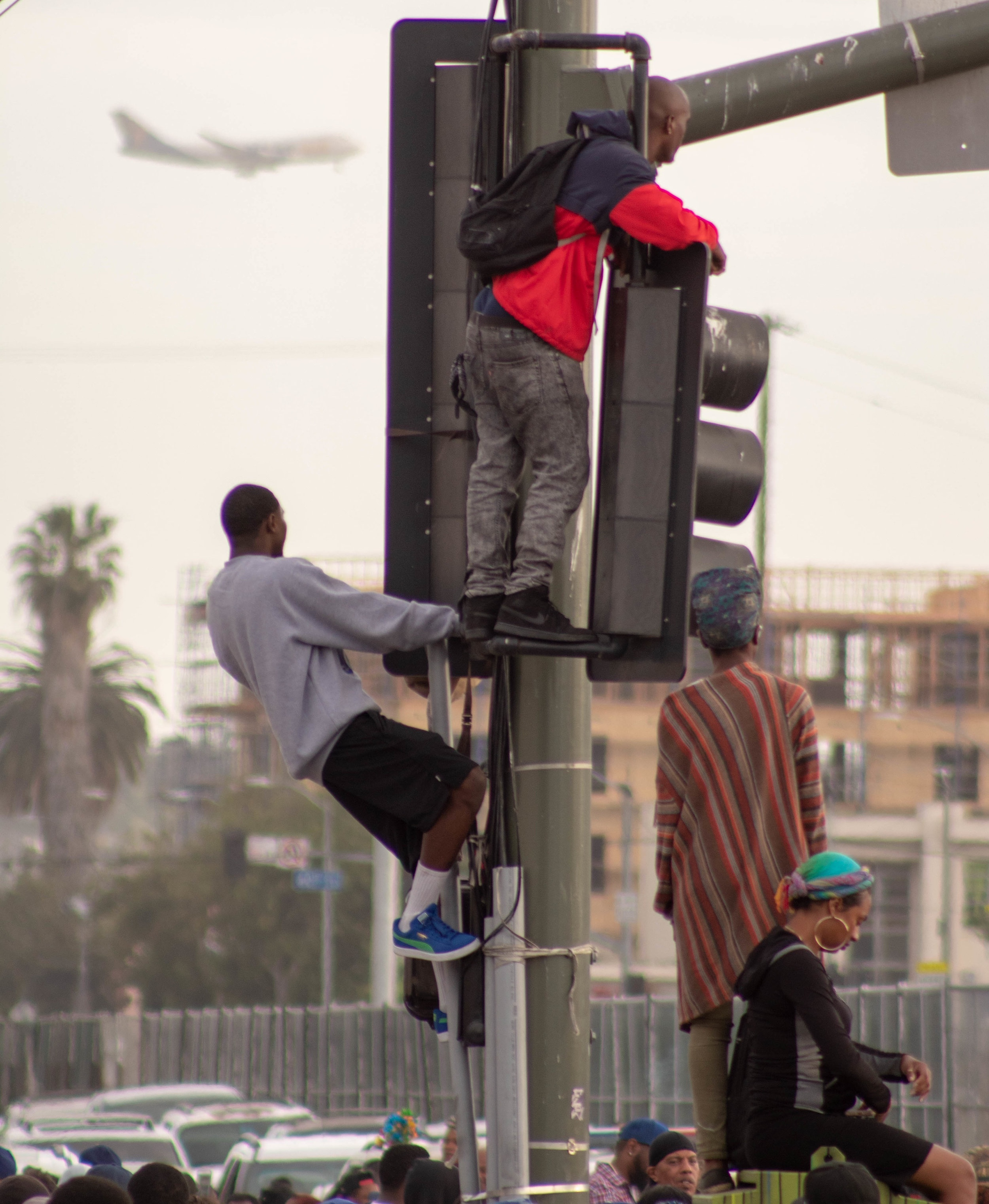 At the corner of Crenshaw and Slauson in South Los Angeles, California, people climbed to the top of traffic lights during the funeral procession of the late rapper Nipsey Hussle on Thursday, April 11, 2019. (Catherine Lima/Corsair Staff)