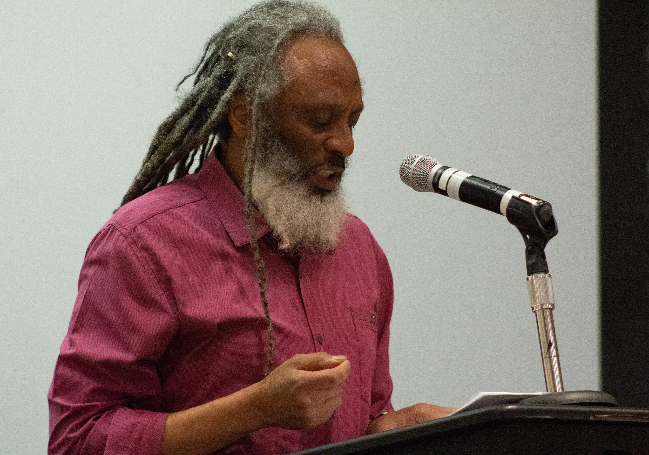 "Wilfred Doucet, an English professor at Santa Monica College, performs a poetry reading during the ""Surreal Borderlines and Portals to Awareness"" event in Stromburg Hall at the SMC main Campus in Santa Monica, California on Thursday, April 18, 2019. Doucet co-founded and facilitated the Dyamsay Writers' Workshop in Santa Monica, the Third Root Writers' Workshop and Artist Showcase in the Pomona Arts Colony, and a poetry reading series at Velocity Cafe in Santa Monica. Today, he shares with the audience ""When Daddy Came Home"", based on his early memories of his father, and ""The Ghost on Ninetieth"", based on the Inglewood community. (Catherine Lima/Corsair Staff)"