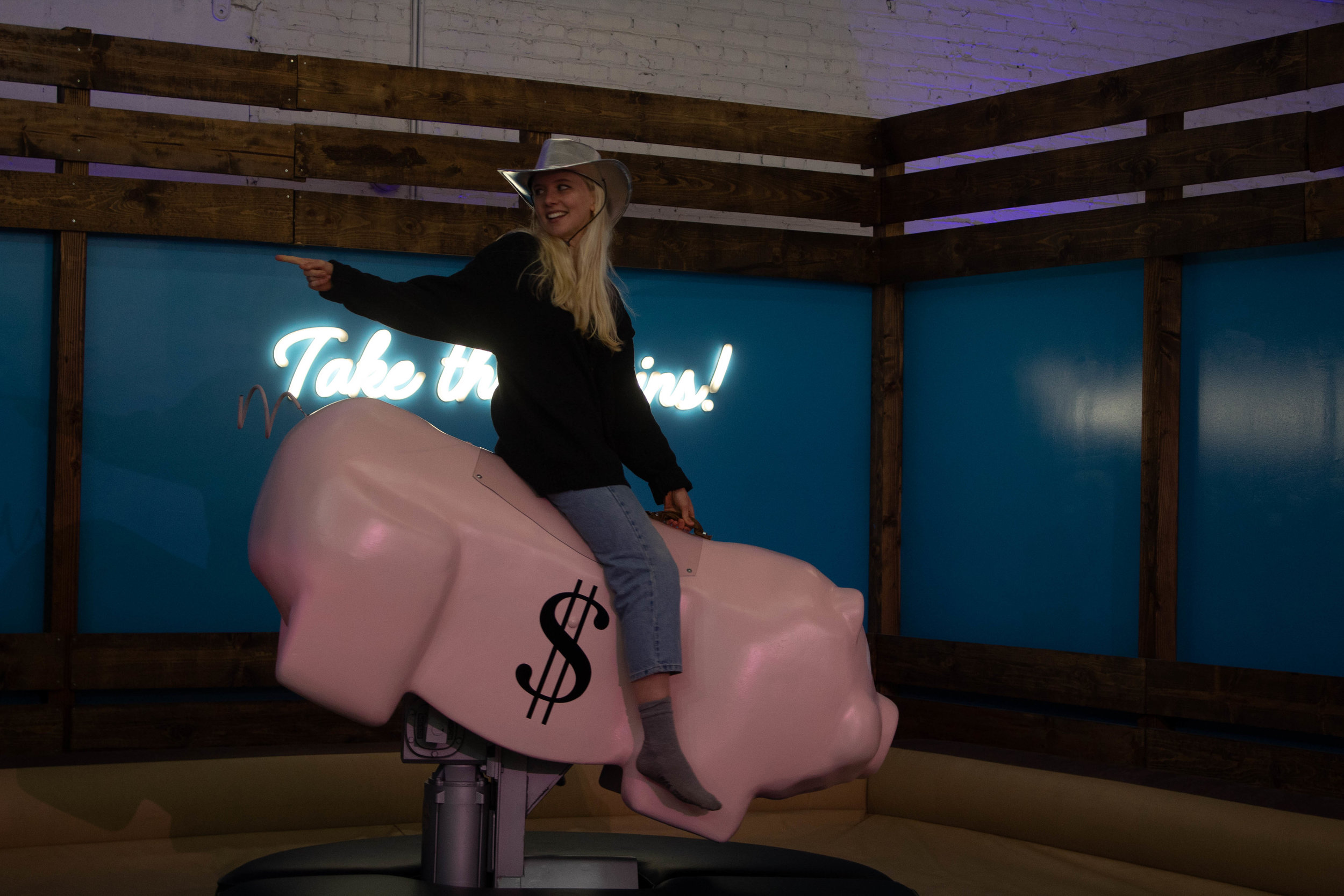 "Tarpley Hitt rides a mechanical piggy bank at Stacks House on April, 16, 2019 in Los Angeles, California. This room encourages attendees to ""Take the reins"" of their financial future. Danica Creahan / The Corsair"
