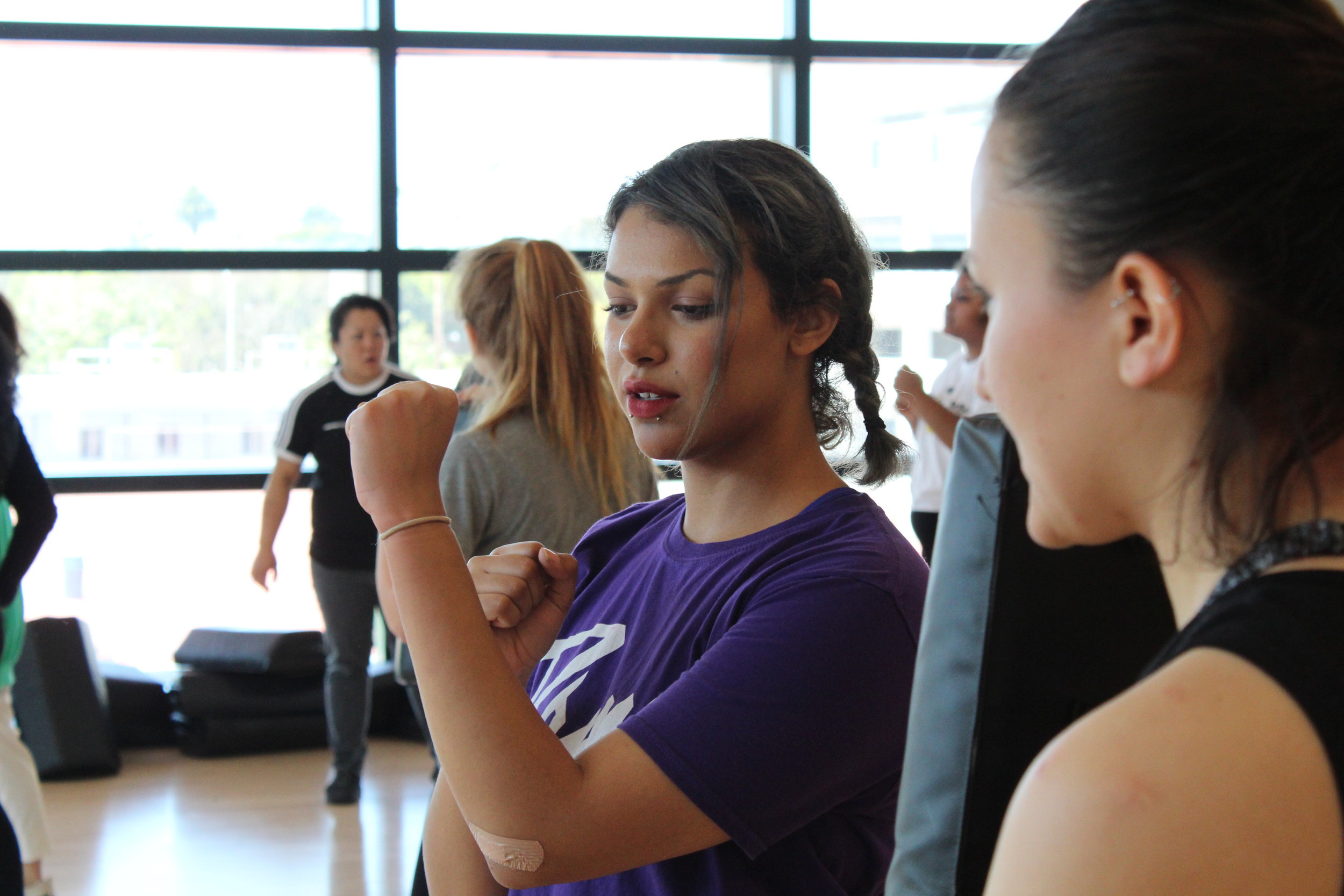 Santa Monica College students practice self-defense maneuvers in the Women's Self Defense course, taught by Jennifer Tanaka (back left), who has been practicing martial arts for 20 years, at Santa Monica College in Santa Monica. The course, KIN PE 41W, meets twice a week for 1.5 hours, and also comes with a semester-long provisional membership at the Kung Fu studio White Tiger, where Tanaka is a student along with fellow SMC Self Defense Professor Blaine Eastcott. (Evan Minniti/The Corsair)