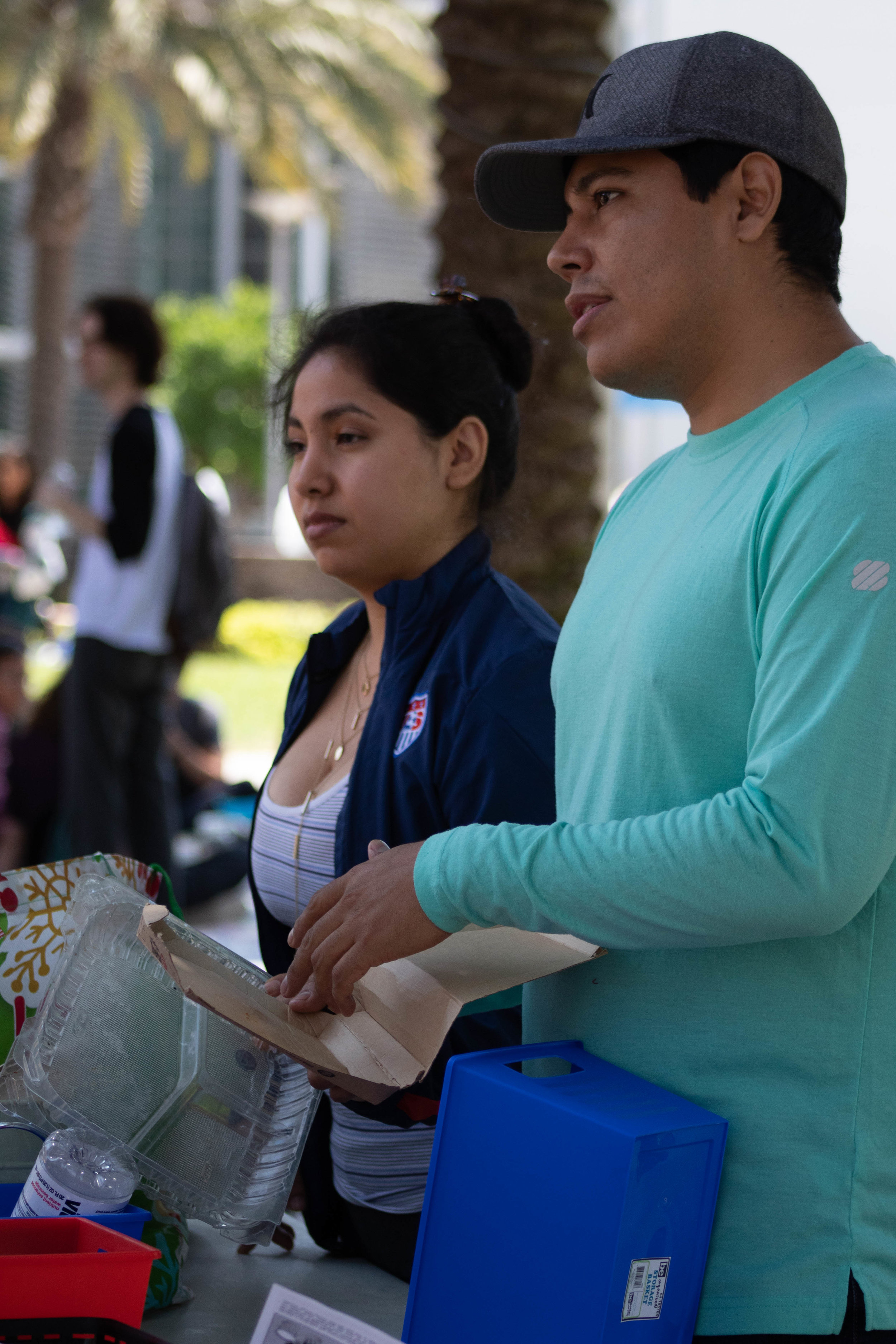 "Patricia Azuci (left), an Industry Engineering student, and Agustin Garcia (right) an Environmental Science student at Santa Monica College are volunteers during the Earth Week Interactive Learning Day at the SMC main campus quad on Wednesday, April 24, 2019 in Santa Monica California. Garcia says, ""We are doing a game that is teaching students how to sort their trash appropriately. There's hazardous material, there's landfill, there's recycling and there's composting. We give them items, and to place them in the appropriate bin there's no right or wrong answer. If they put it in the right bin, we tell them 'congratulations' and if they didn't, we tell them why they did it wrong and tell them exactly what bin they're going into."" (Catherine Lima/Corsair Staff)"