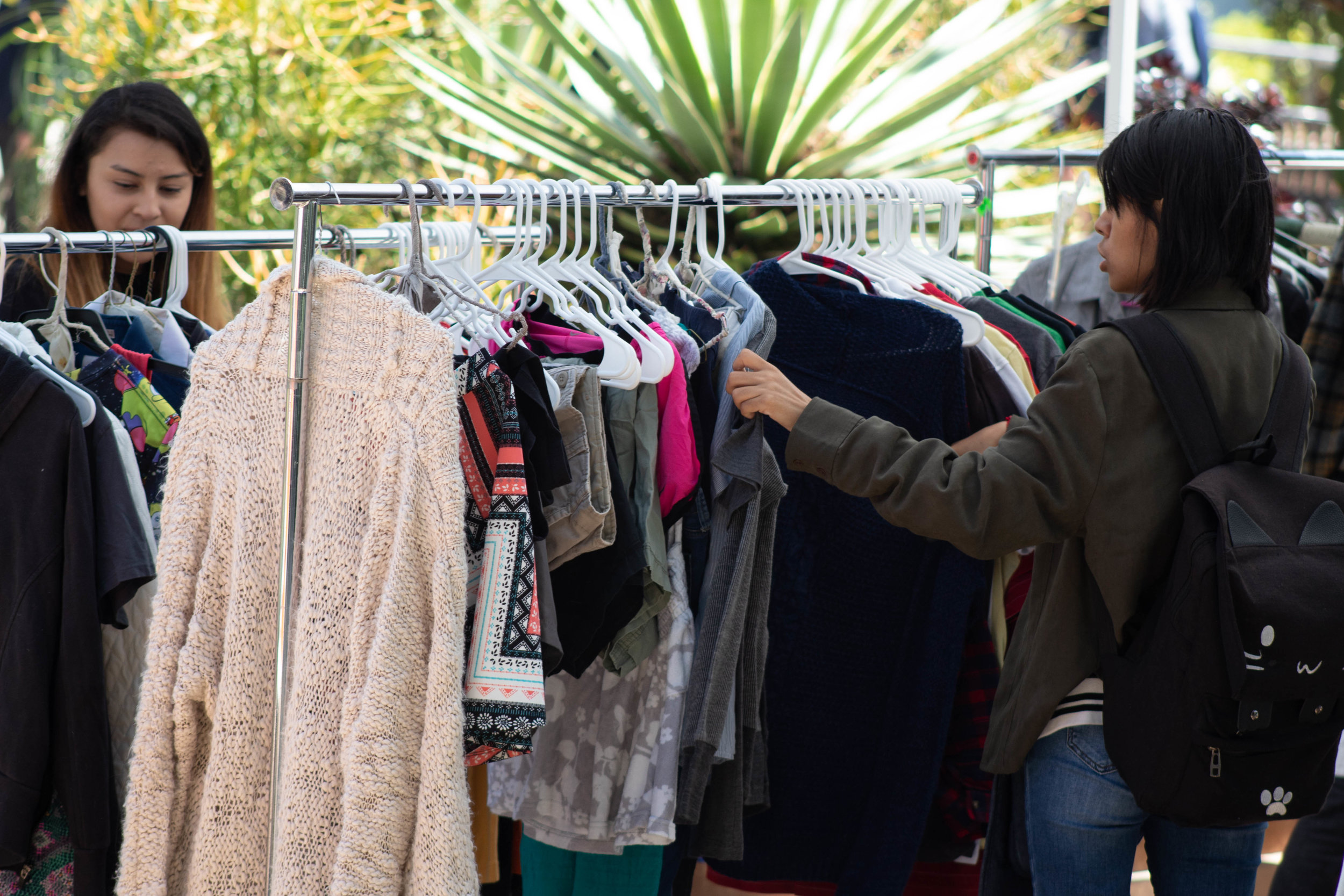 Gicela Gavis (right), a Psychology student, and Dianne Martinez (left), a Nursing student at Santa Monica College take a look at clothes on racks of the Clothing Swap during the Earth Week Interactive Learning Day at the SMC main campus quad on Wednesday, April 24, 2019 in Santa Monica, California. (Catherine Lima/Corsair Staff)