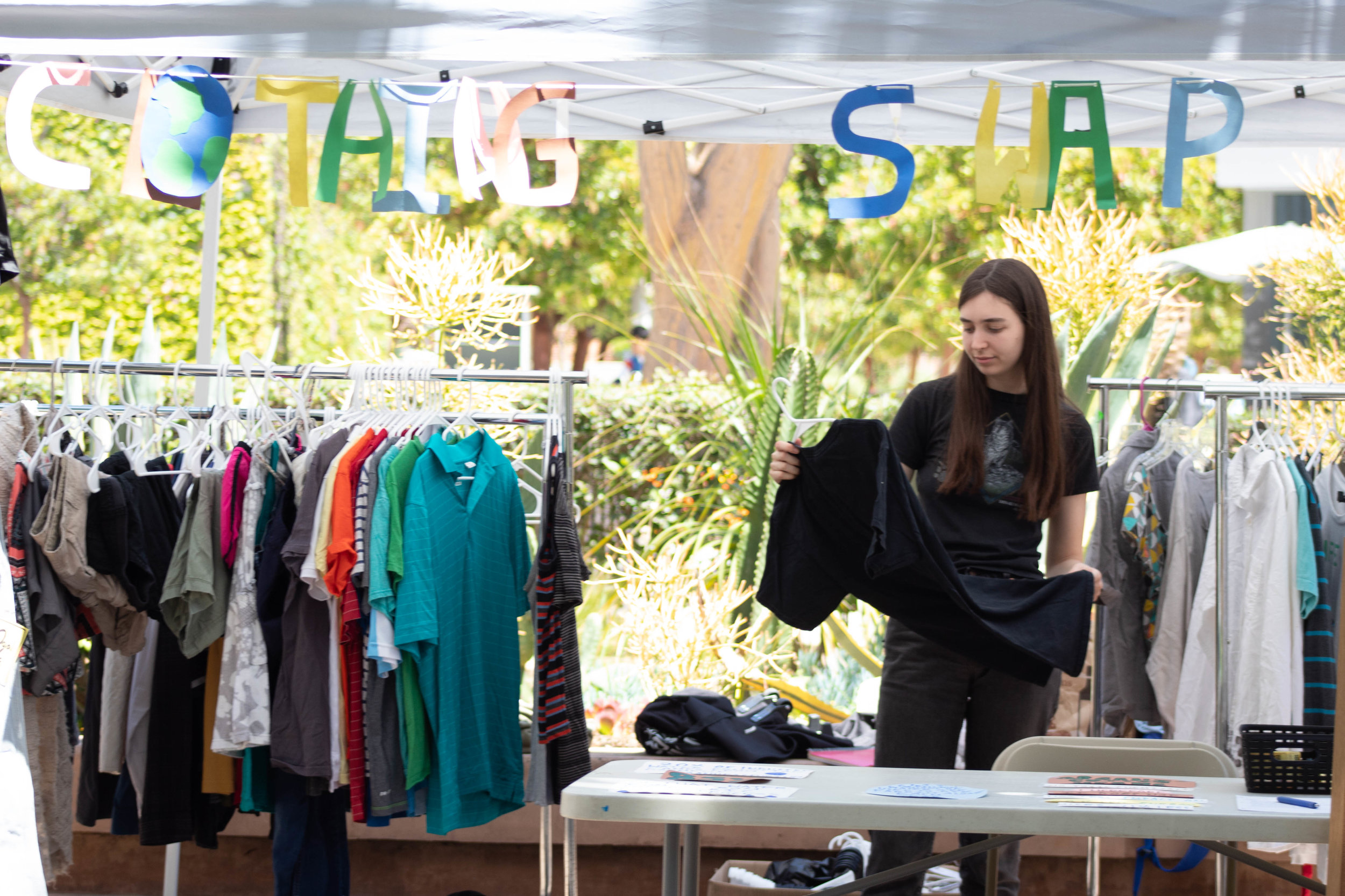 "Jasmine Warren an Environmental Biology student at Santa Monica College hosts a free clothes swap during the Earth Week Interactive Learning Day at the SMC main campus quad on Wednesday, April 24, 2019 in Santa Monica, California. ""People are just coming and donating clothes and taking some,"" says Warren. (Catherine Lima/Corsair Staff)"