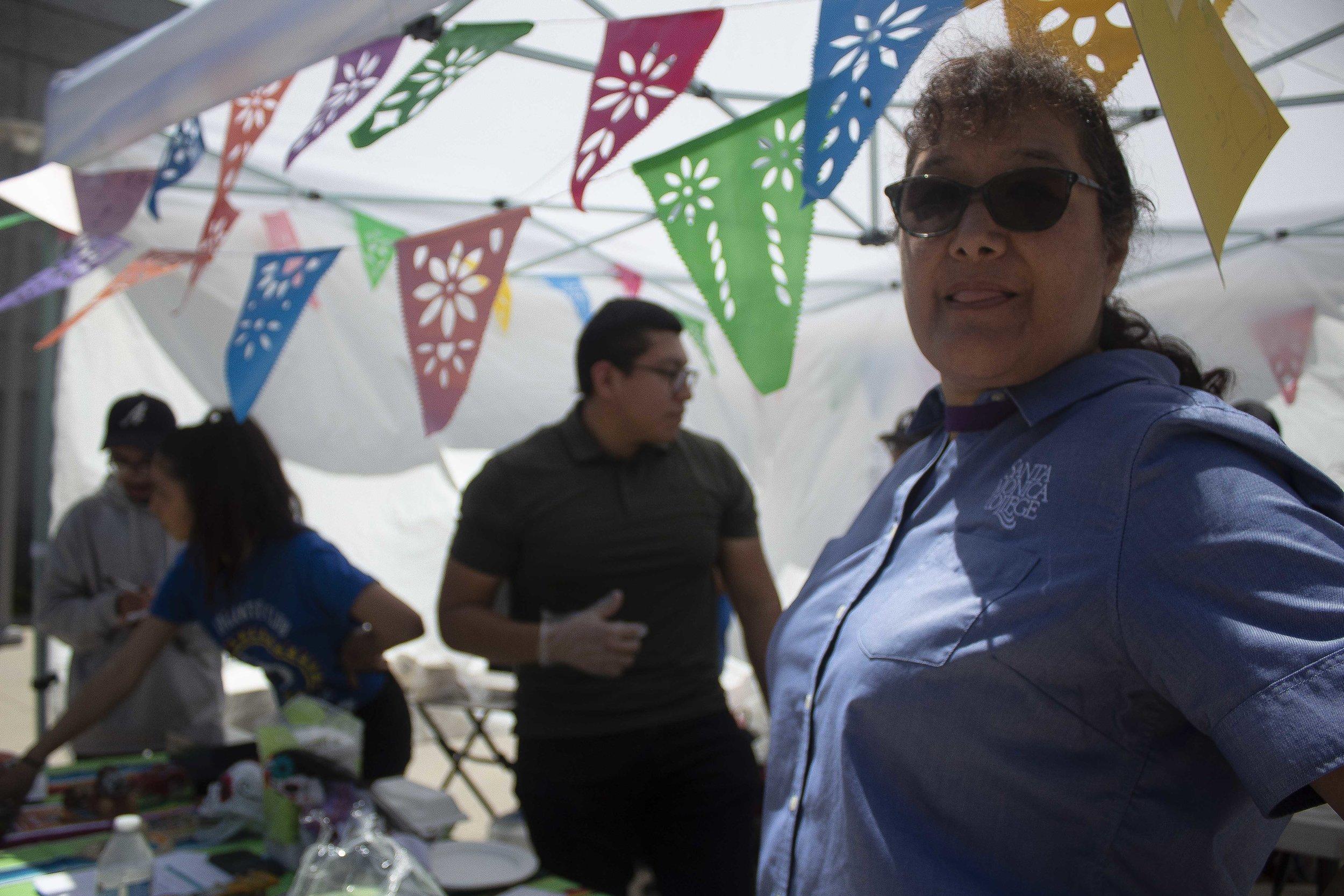 Maria Martinez, advisor of the ADELANTE Program, serves tacos at their booth during the Santa Monica College (SMC) College Fair. April 23, 2019. (Pablo Eden Garcia/ The Corsair)