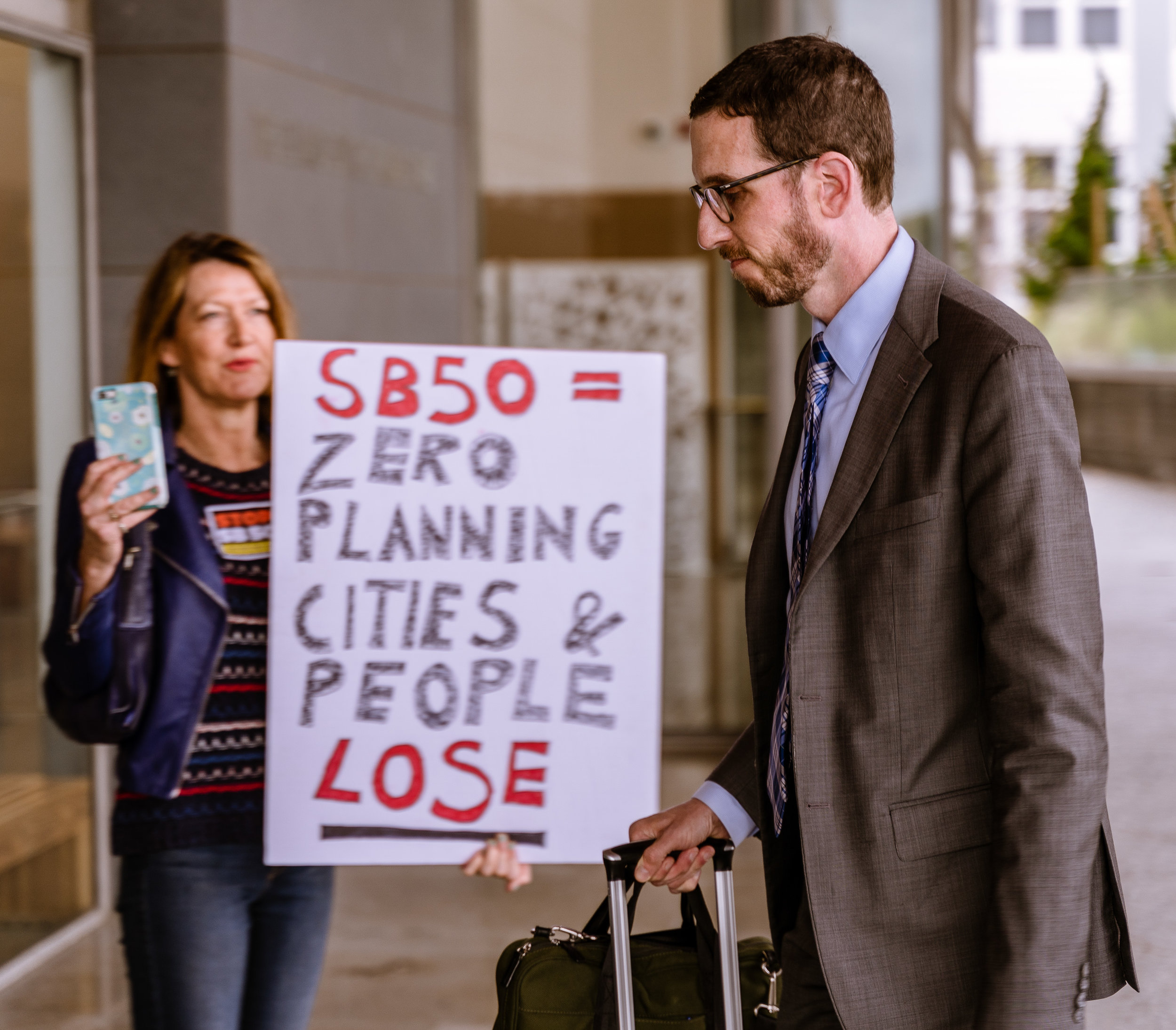 """Lesley O'Toole from Hollywood, by way of Hampshire, England, holds a sign opposing SB-50 and tries to engage with California State Senator Scott Weiner (SD11 – San Francisco), the author of SB-50, but Weiner does not acknowledge her presence as he walks swiftly into the SMC Broad Stage, on Thursday, May 9, 2019. As Weiner passes her, O'Toole adds """"and, you're late"""", although he actually arrived before SB-50 opponent Senator Ben Allen (SD26 – Santa Monica), O'Toole said she was attending tonight because, """"I want to try to save my neighborhood from destruction."""" The SMC Public Policy Institute is presenting its 8th Annual Spring Symposium, """"There Goes the Neighborhood, Part II: How might policy approaches prevent displacement in neighborhoods affected by gentrification?"""" from May 4-9. Tonight's final event in the series is """"Where Goes the Road to Solving California's Housing Crisis? A Keynote Discussion with Legislative Leaders."""" The panel includes California state legislators Senator Ben Allen (SD26 – Santa Monica) and Senator Scott Weiner (SD11 – San Francisco), author of SB 50 which proposes bold approaches to California's housing issues, and Santa Monica Mayor Gleam Davis, a former Co-Chair of Santa Monicans for Renters' Rights and leading advocate for Santa Monica's innovative policy solutions and funding for affordable housing."""" (Glenn Zucman/The Corsair)"""