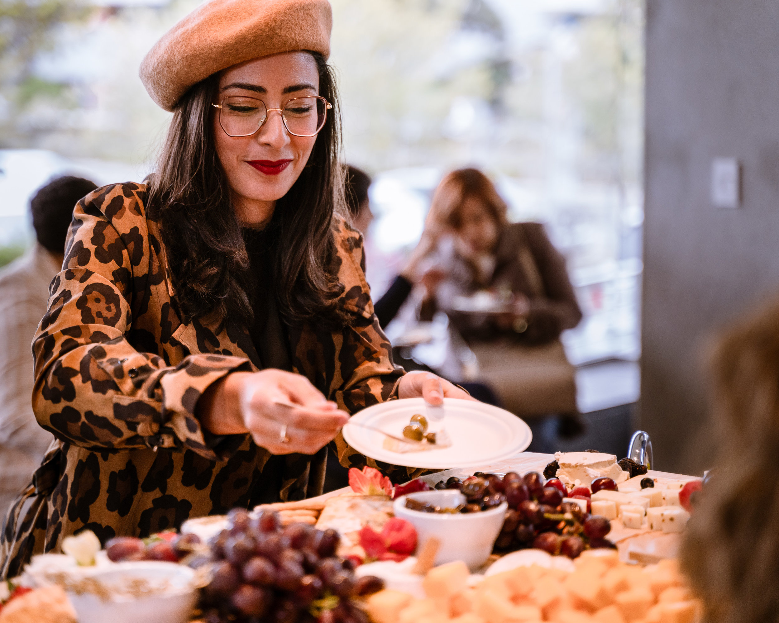 """SMC Fashion Design major Yasmina Sadki from Reims, France serves herself some olives from the hors d'oeuvres table at the reception before tonight's housing discussion at the SMC Broad Stage on Thursday, May 9, 2019. Sadki said that she came partly for the extra credit offered by her SMC Political Science instructor, but that she is """"also very interested in the issues. I hope to be an investor in real estate one day, so I want to understand both sides. Also, I love cheese!"""" The SMC Public Policy Institute is presenting its 8th Annual Spring Symposium, """"There Goes the Neighborhood, Part II: How might policy approaches prevent displacement in neighborhoods affected by gentrification?"""" from May 4-9. Tonight's final event in the series is """"Where Goes the Road to Solving California's Housing Crisis? A Keynote Discussion with Legislative Leaders."""" The panel includes California state legislators Senator Ben Allen (SD26 – Santa Monica) and Senator Scott Weiner (SD11 – San Francisco), author of SB 50 which proposes bold approaches to California's housing issues, and Santa Monica Mayor Gleam Davis, a former Co-Chair of Santa Monicans for Renters' Rights and leading advocate for Santa Monica's innovative policy solutions and funding for affordable housing."""" (Glenn Zucman/The Corsair)"""