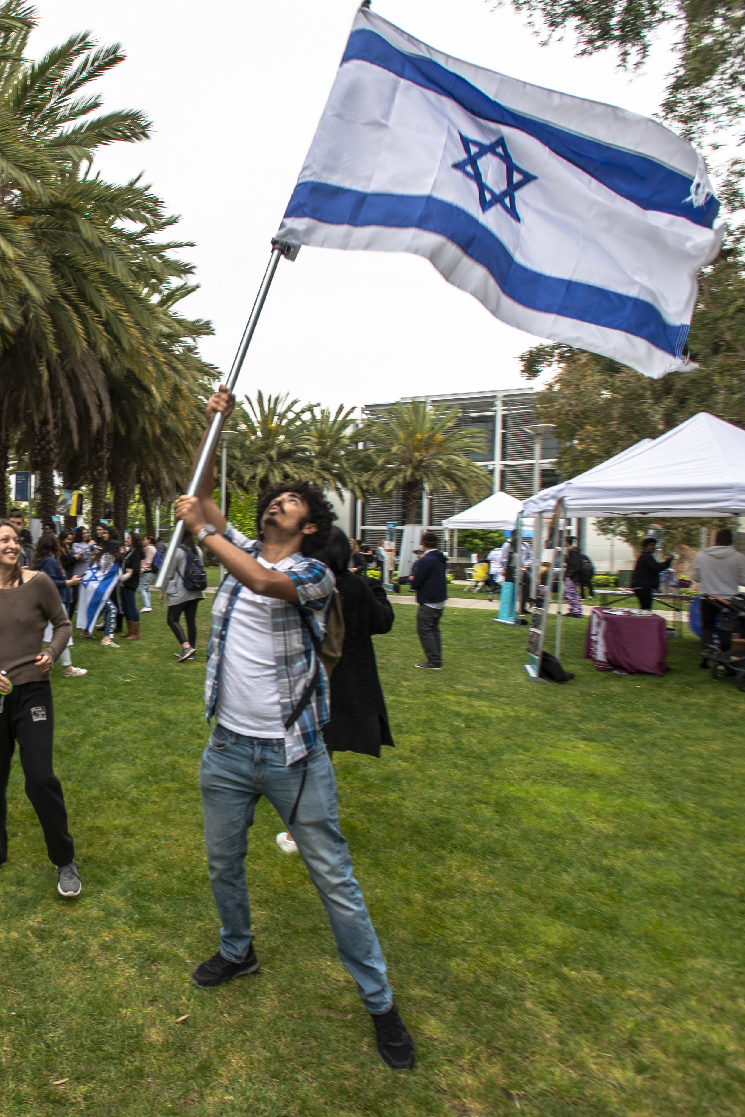 Former Israel Defense Force solider and current Santa Monica College student, Ron waves an Israeli flag to celebrate Israel's Independence Day on Thursday, May 9, 2019.