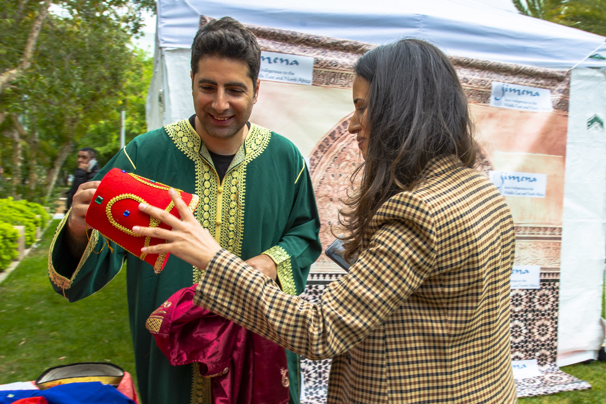 Jews Indigenous to the Middle East and North Africa Los Angeles Program Coordinator, Odin Ozdil (left), shows an israeli Independence Day participant a traditional Fez hat on Thursday, May 9, 2019.
