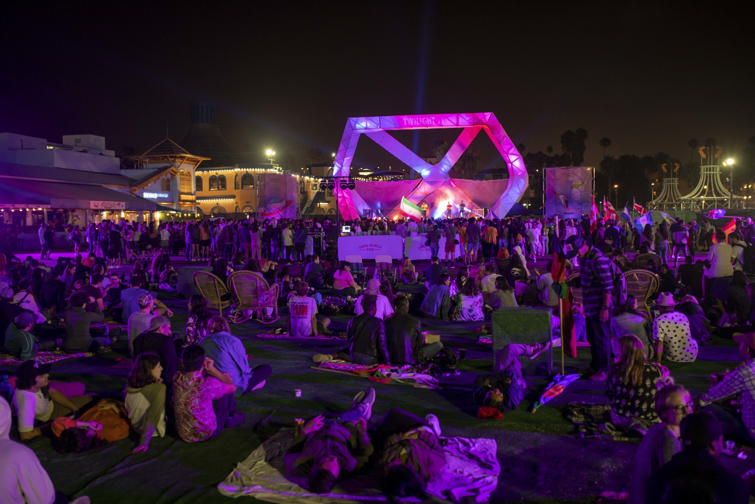 """Concert goers relax in the synthetic grass section during the """"Twilight on the Pier"""" concert series on the Santa Monica Pier in Santa Monica, California. (Josh Nicoloro/The Corsair)"""