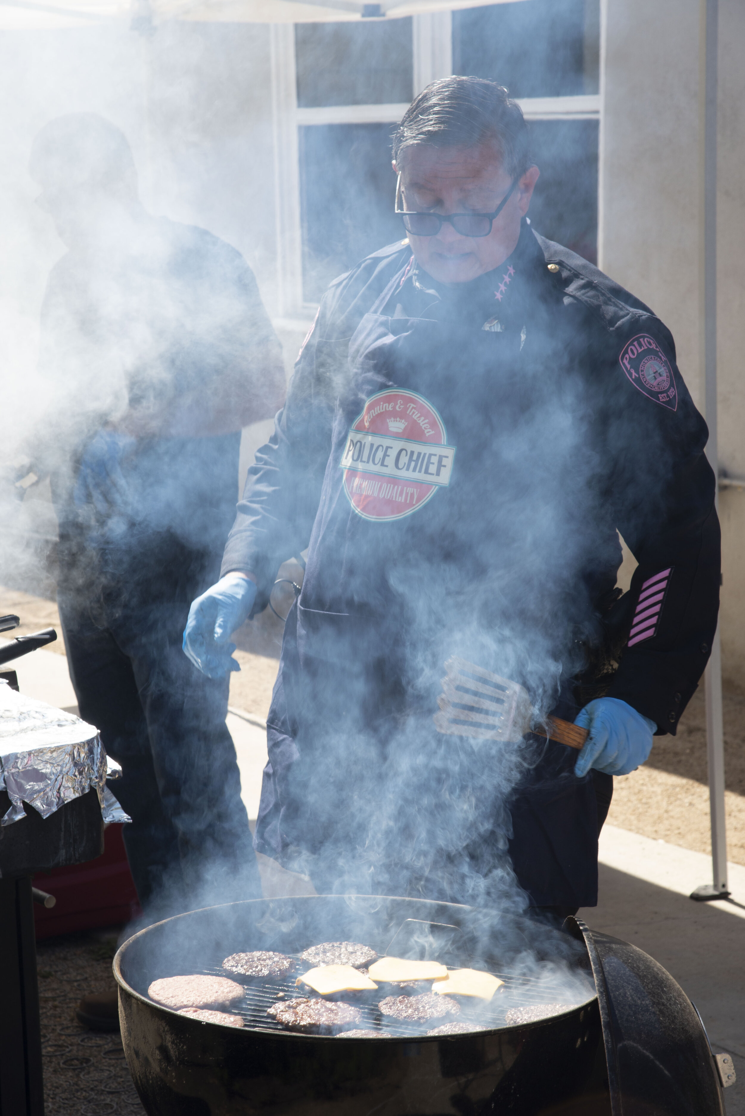 SMC Chief of Police, Johnnie Adams, endures the smoke and heat to prepare burgers and hot dogs at the barbecue on Tuesday, October 8th, 2019 at their headquarters across from Santa Monica College, in Santa Monica, California.  (Rachel O'Brien/The Corsair)