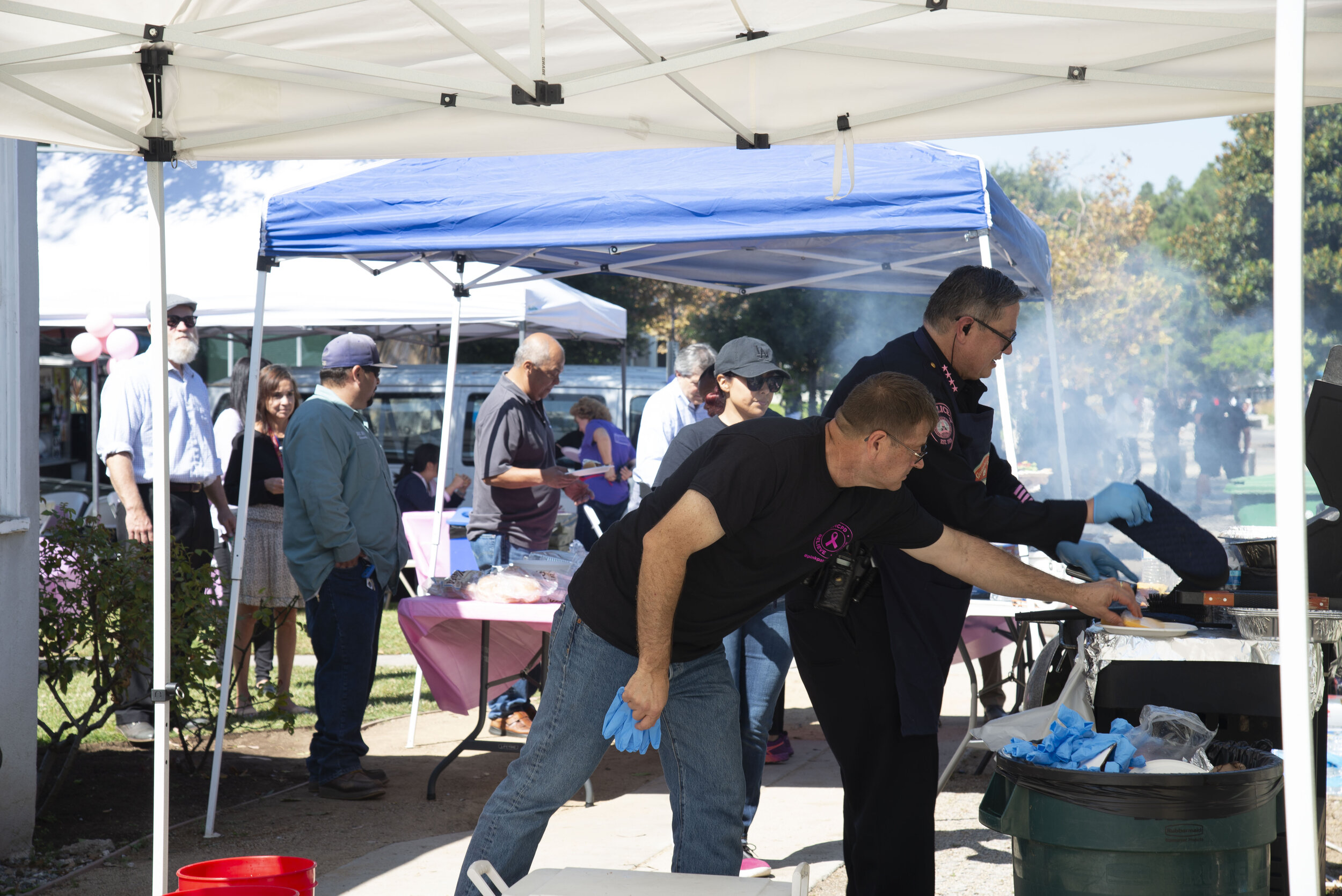 SMC Chief of Police, Johnnie Adams (R), and Captain Vince Carter (L), prepare burgers and hot dogs at the SMC Police Department barbecue and fundraiser.  (Rachel O'Brien/The Corsair)