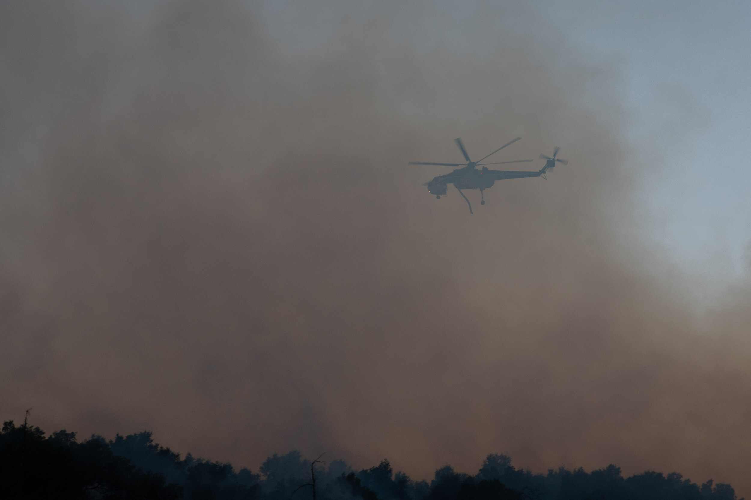 A helitanker behind a cloud of smoke just before it drops water on the Saddlerige Fire just off interstate 5 near Newhall Calif. on Friday, Oct. 11, 2019. (Conner Savage/The Corsair)