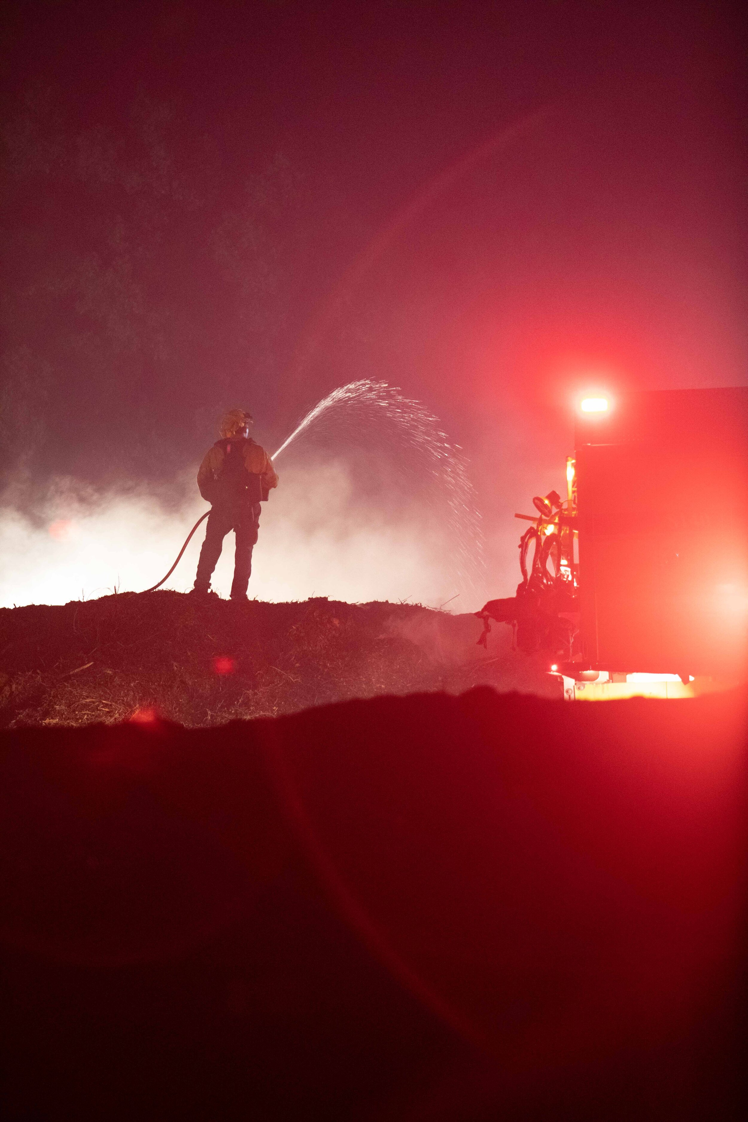 A firefighter works to extinguish a brush fire raging as part of the Saddleridge fire on the evening of Saturday, Oct. 12, 2019 beside the 5 freeway, just north of Sylmar, Calif. in the Newhall Pass. (Joshua Nicoloro/The Corsair)