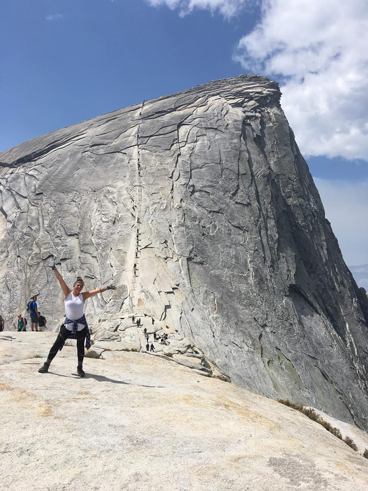 Mia standing on the subdome, with the Half Dome cables behind her
