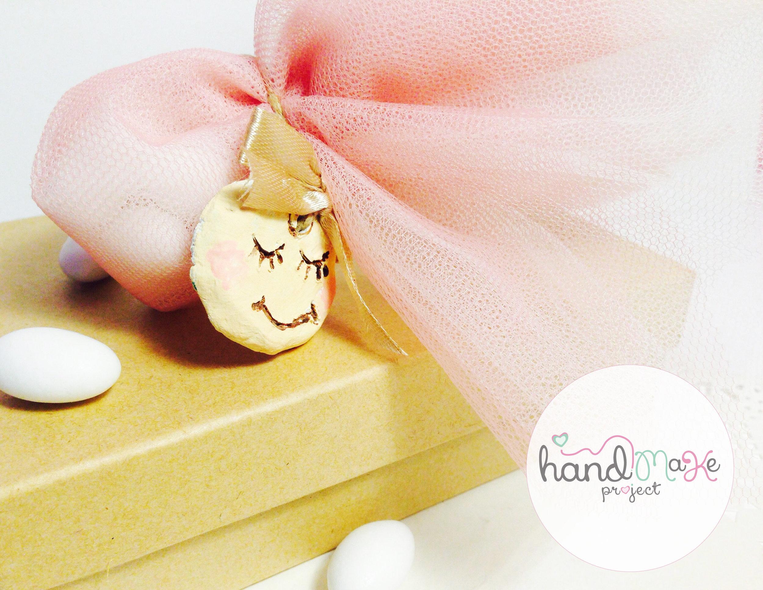 κωδικός ΒΒ_ 46 Collection ''Playful''   Μπομπονιέρα με χειροποίητο πήλινο διακοσμητικό σε σχήμα μωρό, σπάγγο, τούλι λευκό-σάπιο μήλο και σατέν χρυσή κορδέλα.