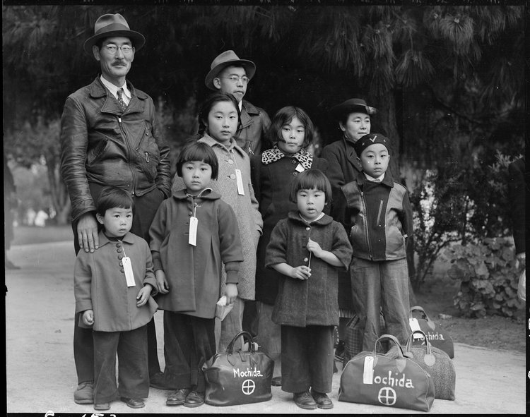 May 8, 1942. Hayward, California. Members of the Mochida family awaiting evacuation bus. Identification tags are used to aid in keeping the family unit intact during all phases of evacuation. Mochida operated a nursery and five greenhouses on a two-acre site in Eden Township. He raised snapdragons and sweet peas. Evacuees of Japanese ancestry will be house in War Relocation Authority centers for the duration. National Archives.