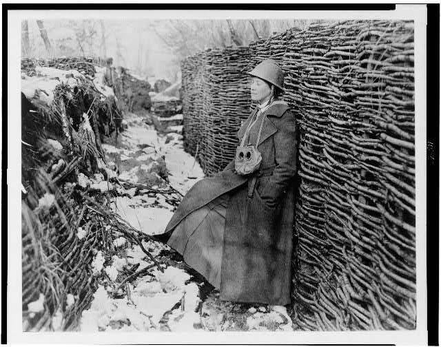 Helen Johns Kirtland in trench during World War I; she is wearing a helmet and great coat, and has a gas mask hanging around her neck . Between 1914 and 1918.