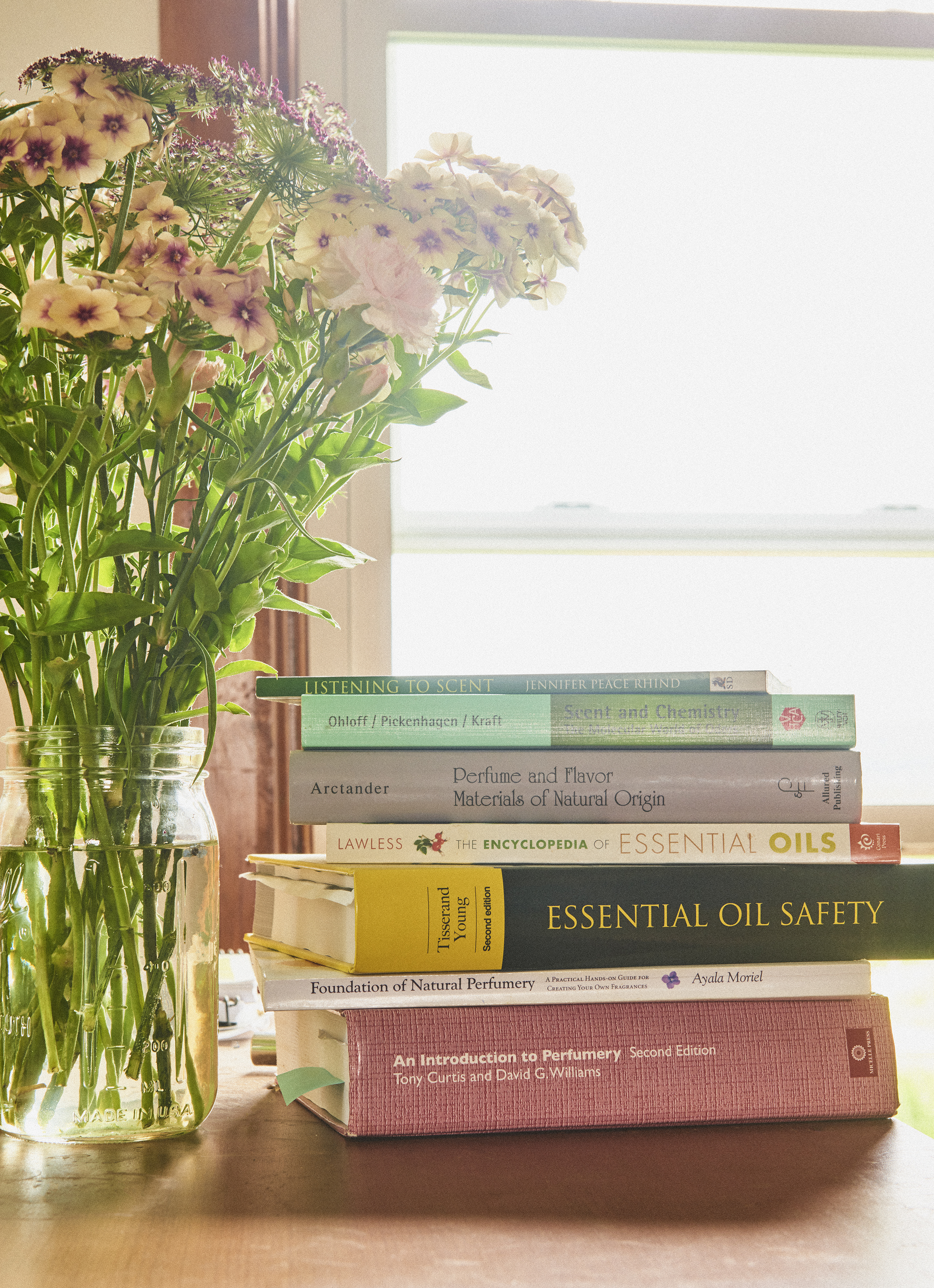 Perfume books and flowers sitting on a desk