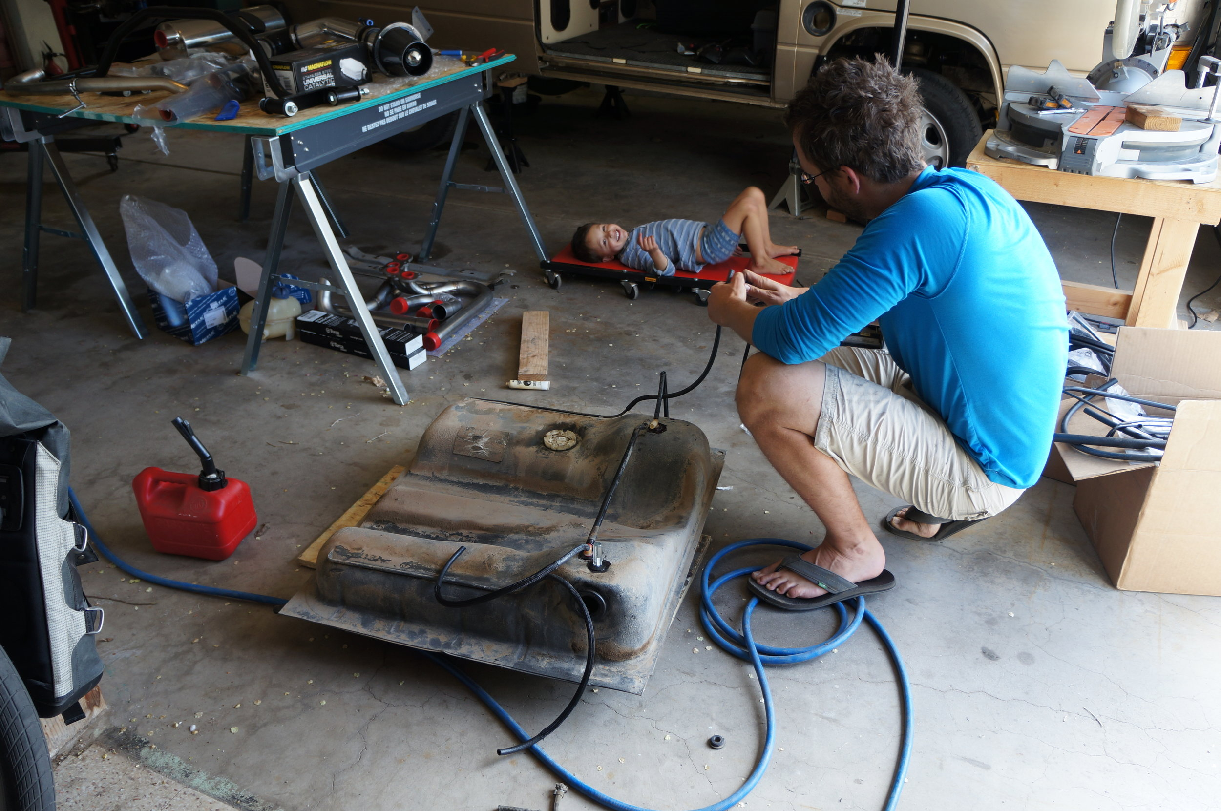 April 2017 - Bennett supervising Chip's effort at putting the gas tank back together. Nothing like filling ALL the way up and not dripping gas for the next 20 miles.